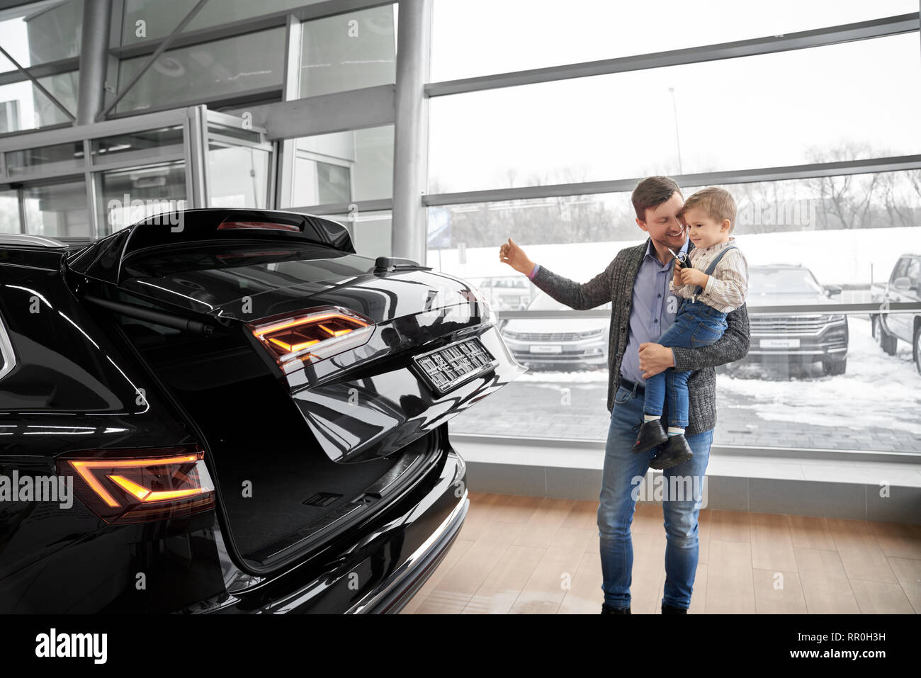 Parent and child observing new expensive automobile in modern car dealership showroom. Happy father standing, holding son on hands, closing car trunk of black vehicle. - Stock Image