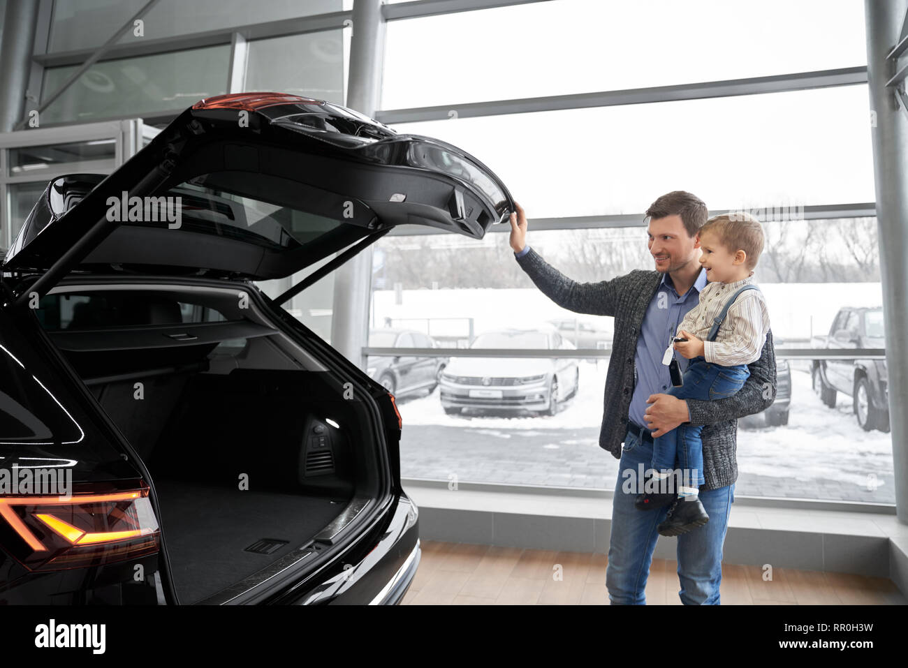 Cheerful father holding kid on hand, showing to son new black car. Handsome man opening empty car trunk of expensive black automobile. Parent and child smiling, looking at car. - Stock Image