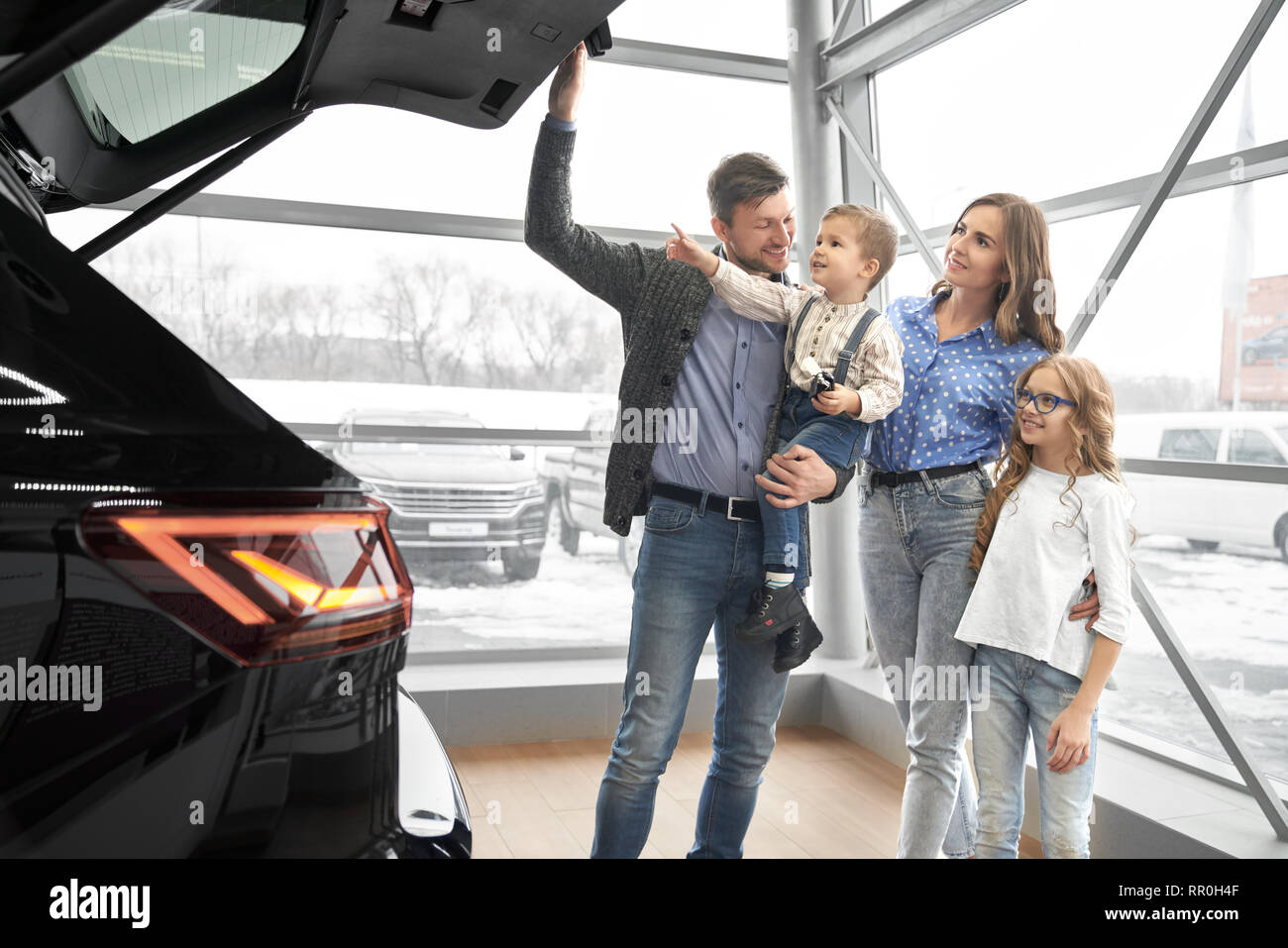 Happy family observing new, expensive black car in modern showroom. Father holding kid on hand, opening car trunk, parents standing with children, smiling, looking at car. - Stock Image