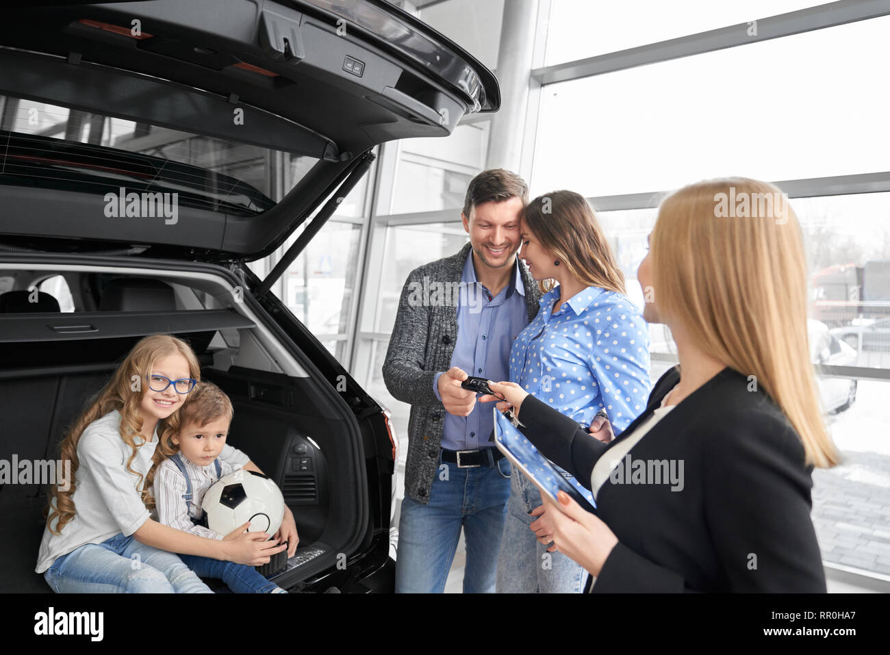 Car dealer of dealership showrrom working with clients, holding folder and giving car keys to buyers of vehicle. Couple standing, posing, daughter and son sitting in car trunk, hugging, smiling. - Stock Image