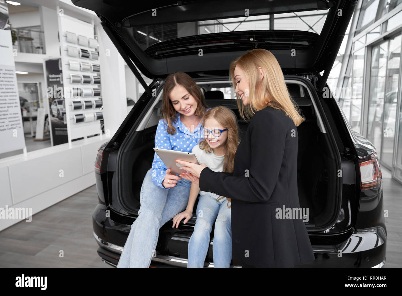 Car dealer working with clients, instructing, showing information on gadjet. Mother and daughter sitting in car trunk, communicating with manager of dealer showroom, smiling, posing. - Stock Image