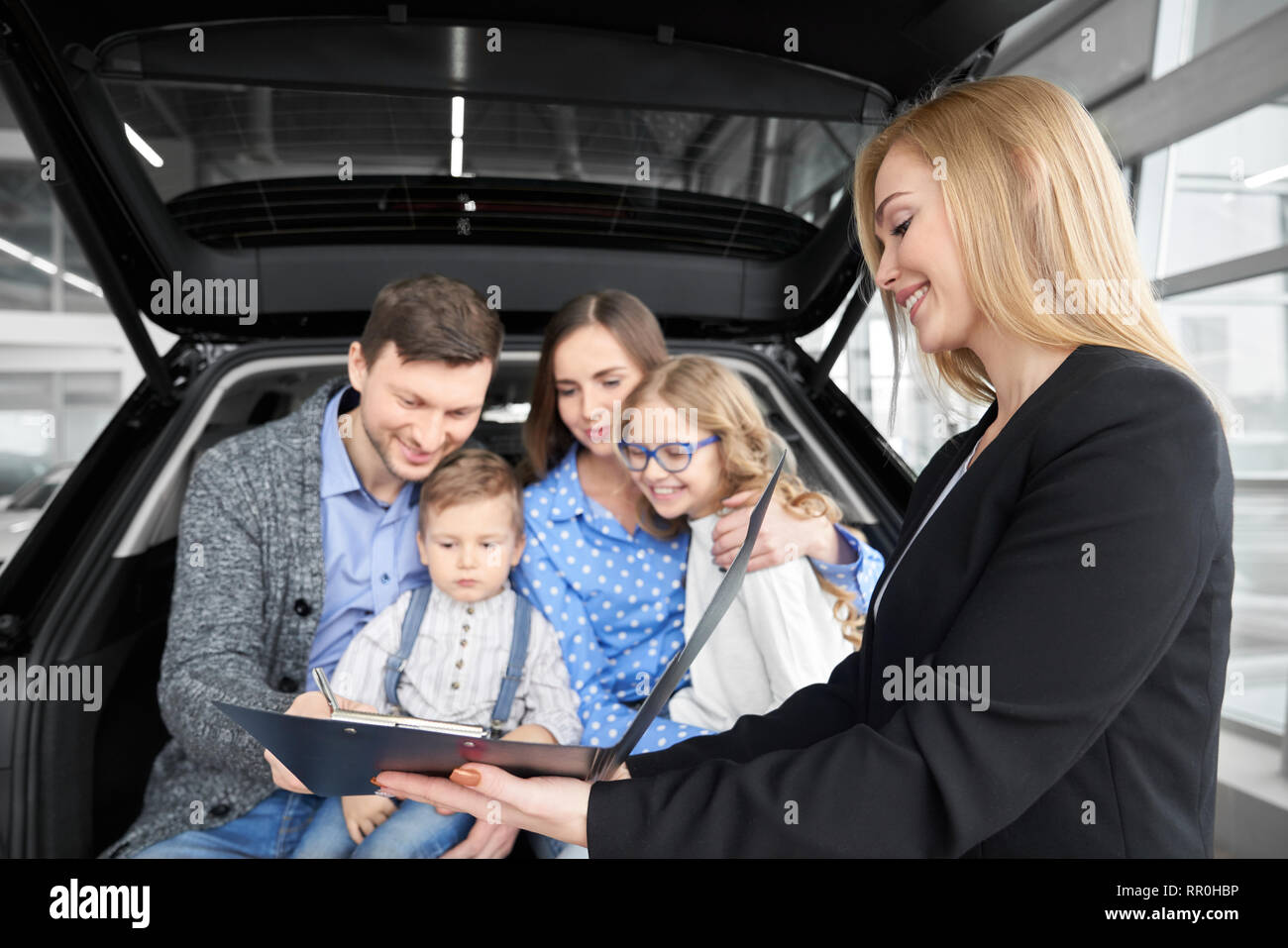 Happy family sitting in car trunk, buying new automobile in car dealership. Beautiful woman, car dealer holding black folder with document. Man signing contract, purchasing vehicle. - Stock Image