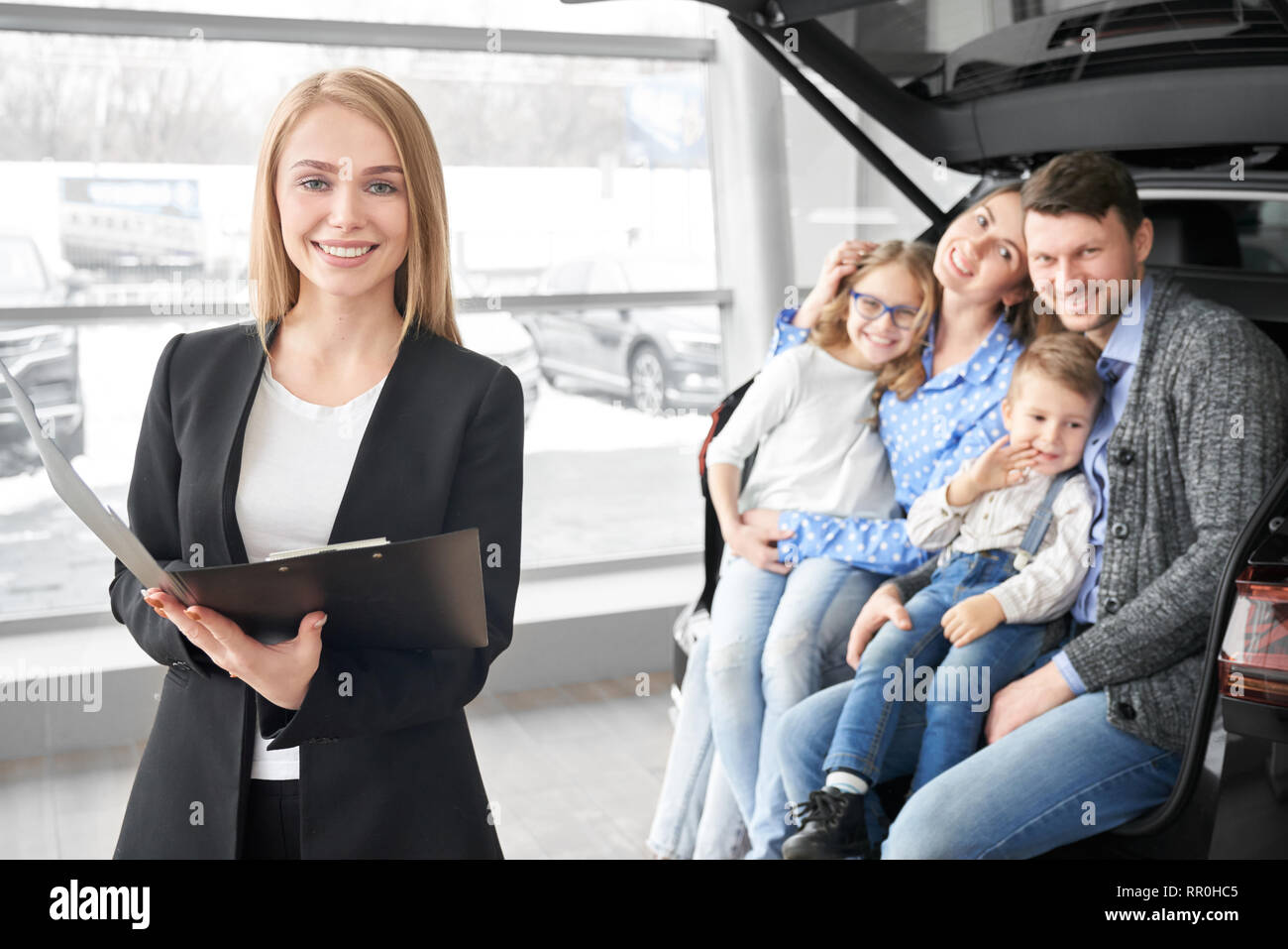 Happy family looking at camera, smiling and sitting in trunk of new automobile. Manager, beautiful woman working in dealership showroom with potential buyers of cars. Blonde holding folder, posing. - Stock Image