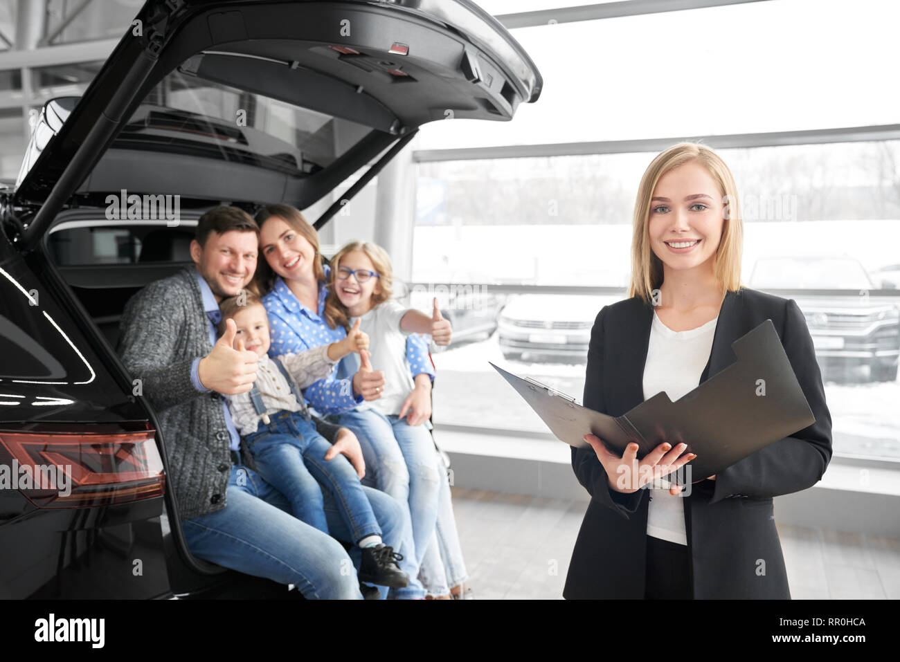 Car dealer, beautiful blonde woman standing, holding folder and posing. Happy family sitting in car trunk, smiling, looking at camera and showing thumbs up, buyers of automobile. - Stock Image