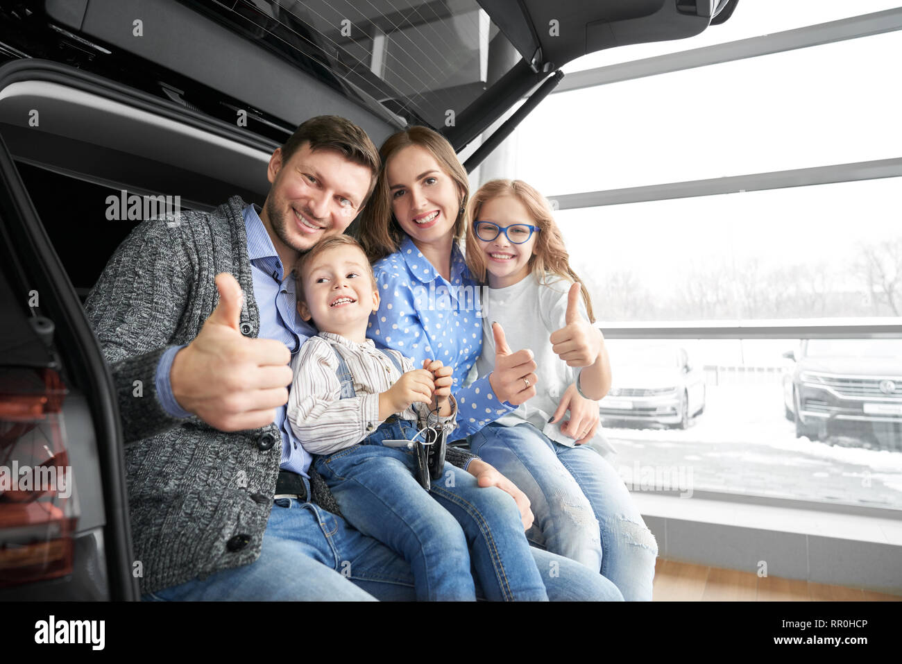 Happy family of mother, father, son and daughter sitting in trunk of new automobile. Potential buyers of vehicle. Parents and children looking at camera, smiling and showing thumbs up. - Stock Image