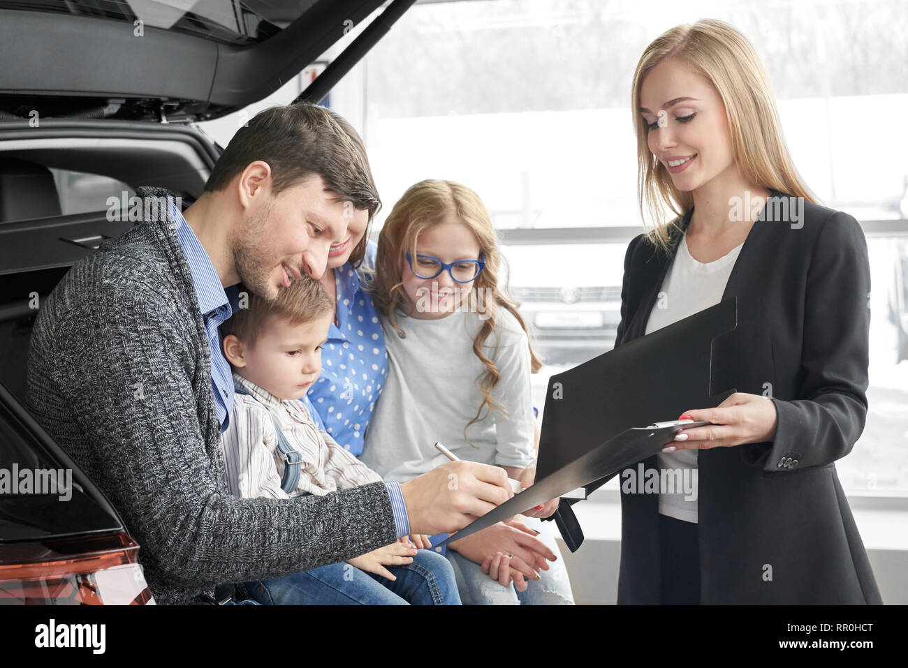 Beautiful woman working as car dealer, holding black folder with document. Man signing contract, purchasing vehicle. Happy family sitting in car trunk, buying new automobile in car dealership. - Stock Image