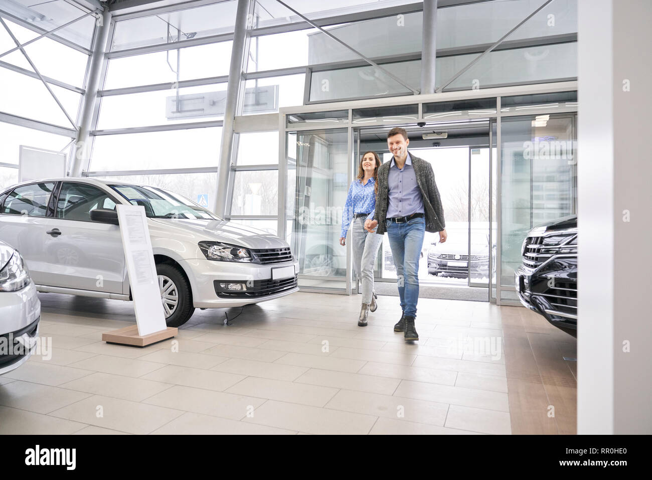 Beautiful couple walking in dealership showroom, holding hands and going. Charming woman and beautiful man smiling, posing and observing automobiles in car center. - Stock Image