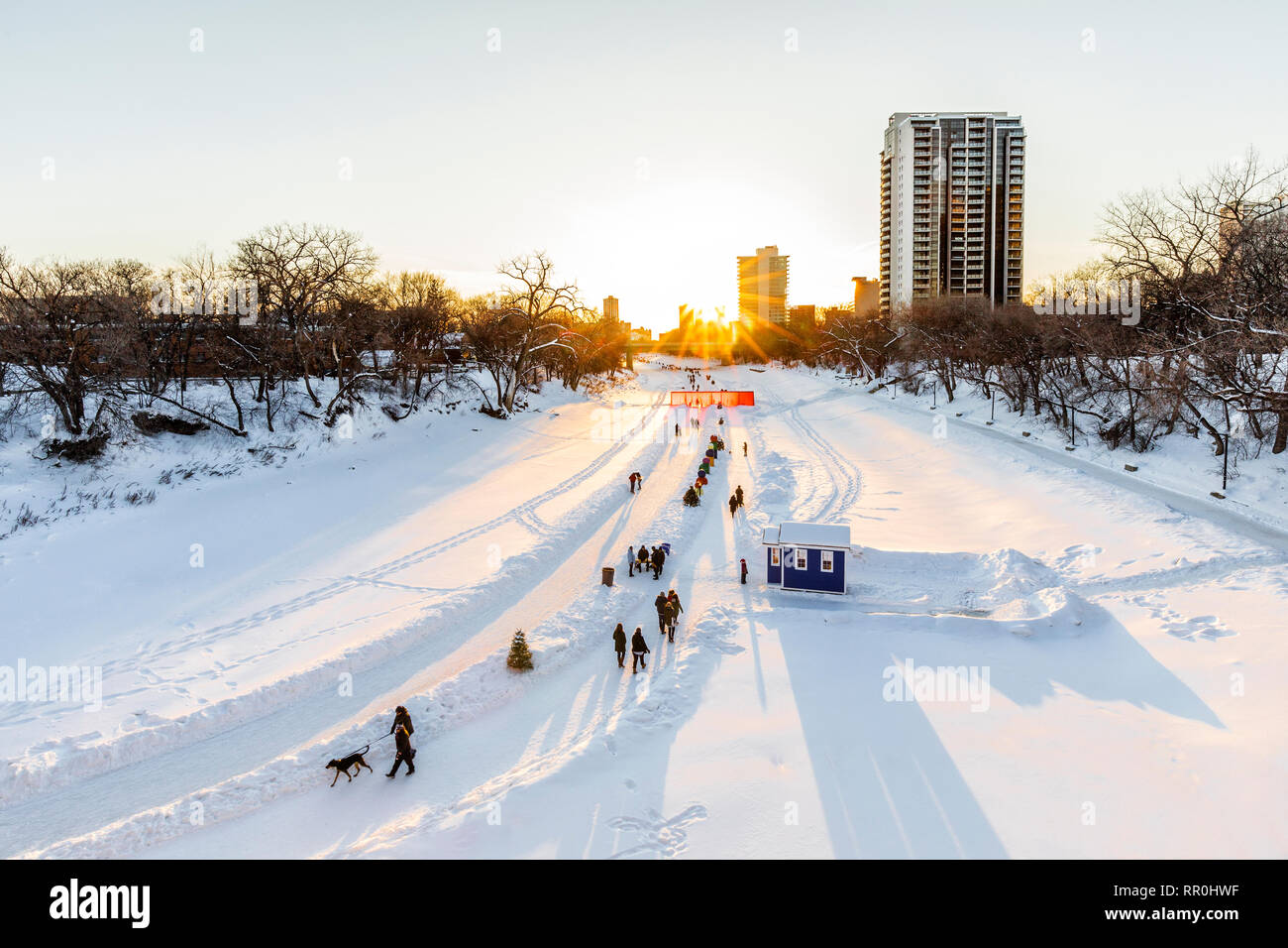 Walkers, hikers and ice skaters on the Assiniboine River Trail at sunset, part of the Red River Mutual Trail, The Forks, Winnipeg, Manitoba, Canada. - Stock Image