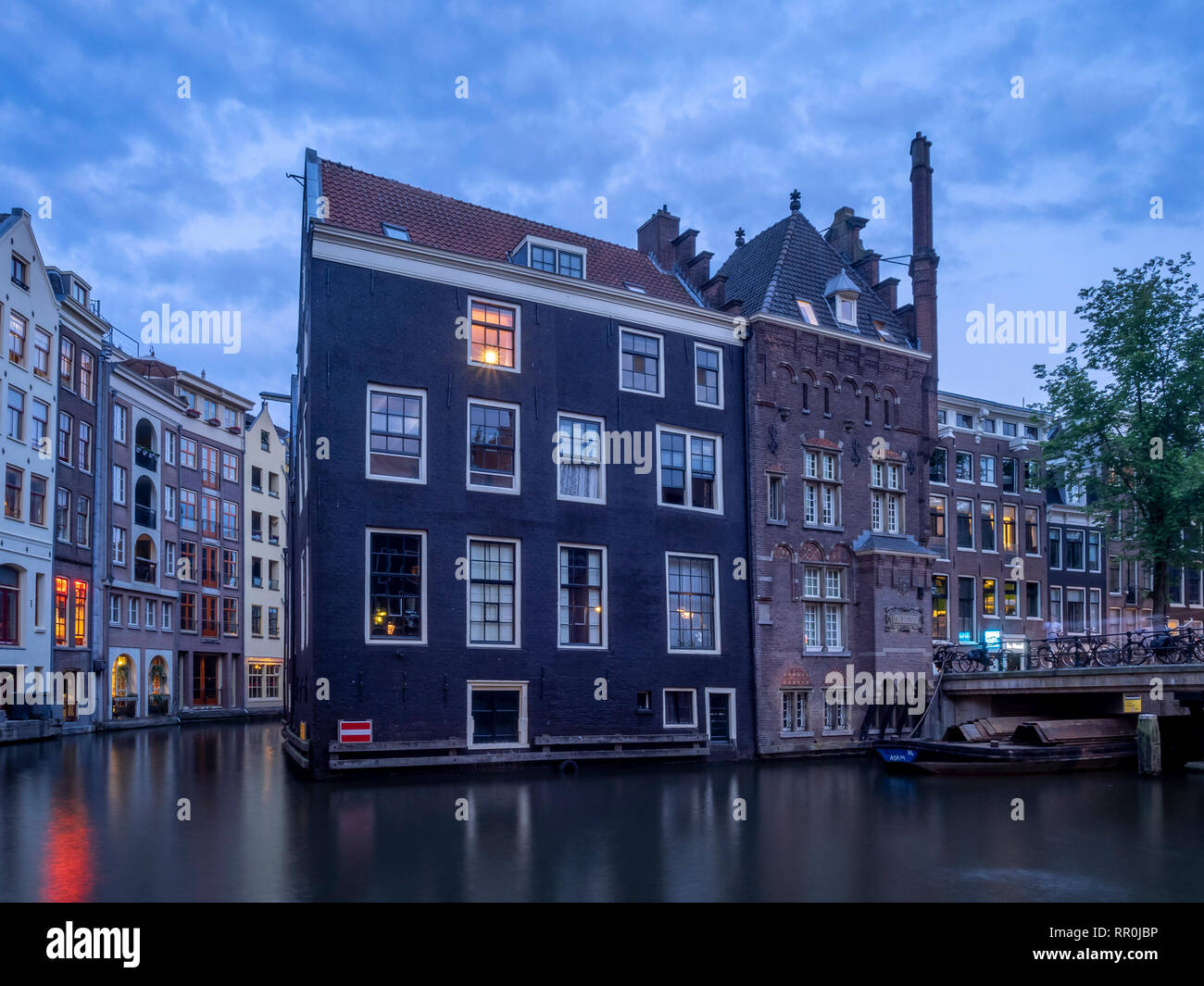 Traditional canal houses at dusk in Amsterdam. Buildings on the canal are a form of traditional Dutch architecture. - Stock Image
