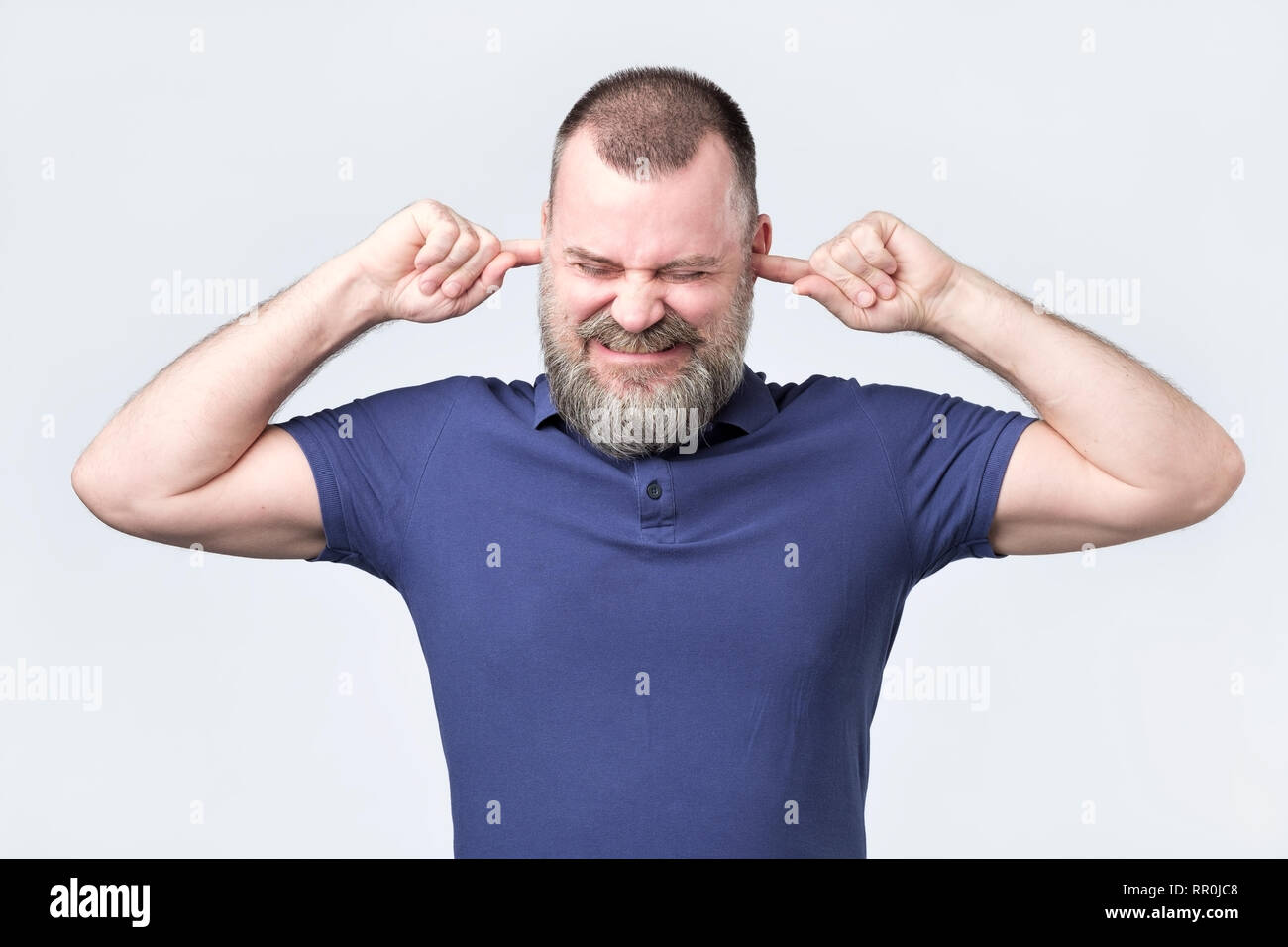 Senior man, covering closed ears annoyed by loud noise not wanting to hear story - Stock Image