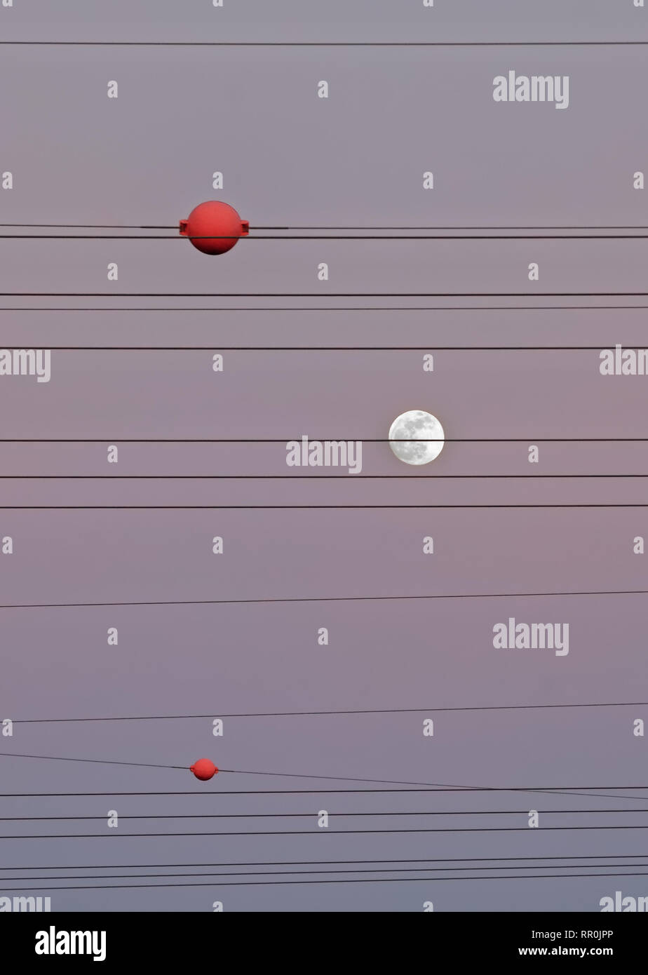 Power lines are marked by red balls, the full moon is arranged like one of the red balls, evening light in pink-violet shades - Location: Germany - Stock Image
