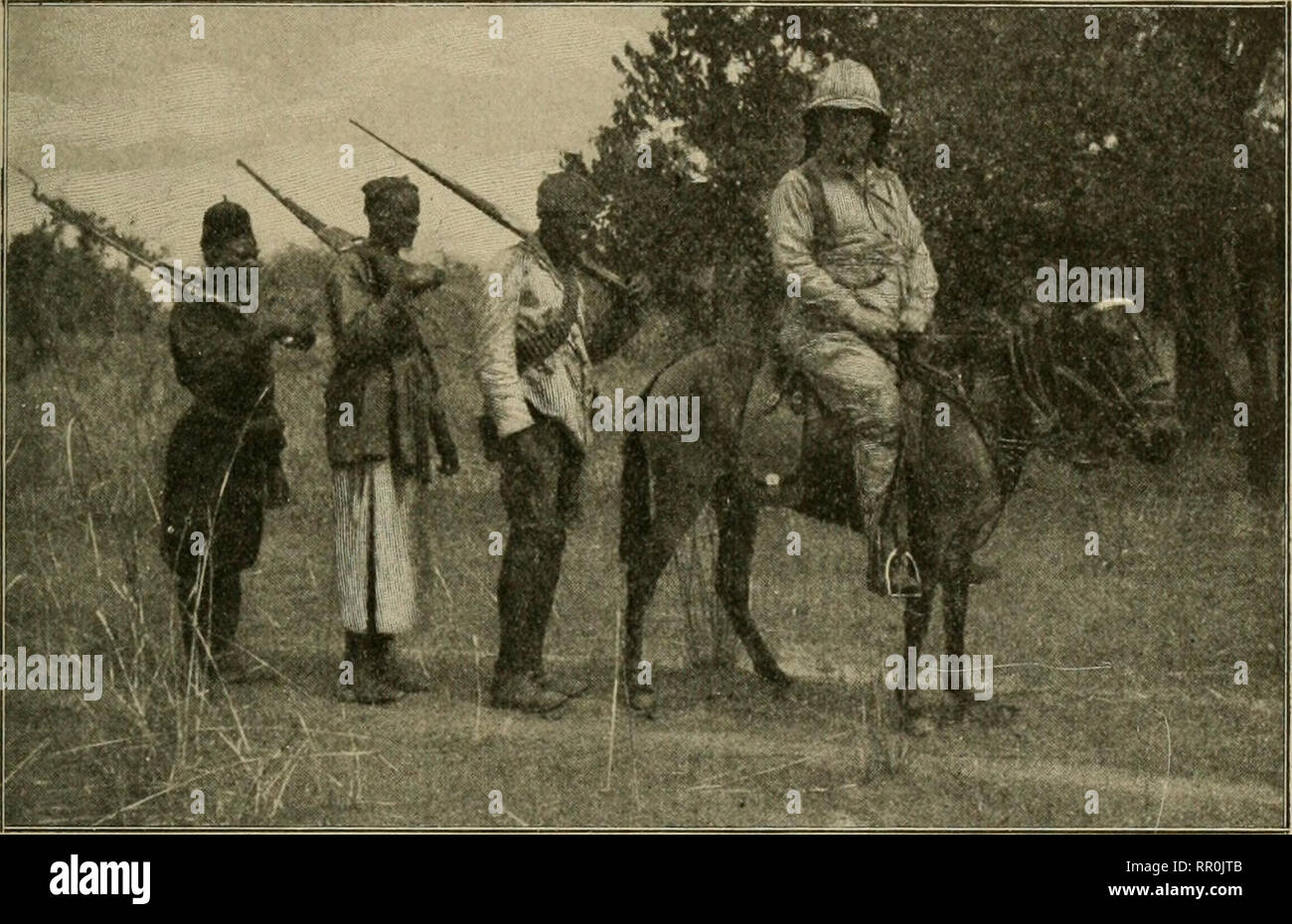 . African game trails;. Hunting. DOWN THE NILE; THE GIANT ELAND 511 some slivers of wood and boiled our tea; and our two meals, breakfast and dinner, were taken at a table in the open, under a tree. We had with us seven black soldiers of the Belgian native troops, under a corporal; they came from every quarter of the Congo, but several of them could speak Swahili, the lingua franca of middle Africa, and so Kermit could talk freely with them. These black soldiers be-. Thc letuin tu Redjaf, Belgian askari in tht; rear From a photograph by Kermit Roosevelt haved excellently, and the attitude, bot - Stock Image