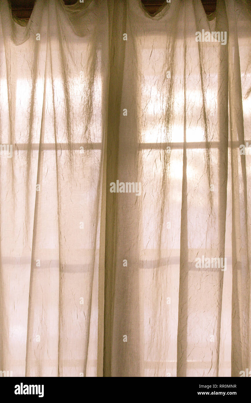 Sheer fabric window curtain with filtered light - Stock Image
