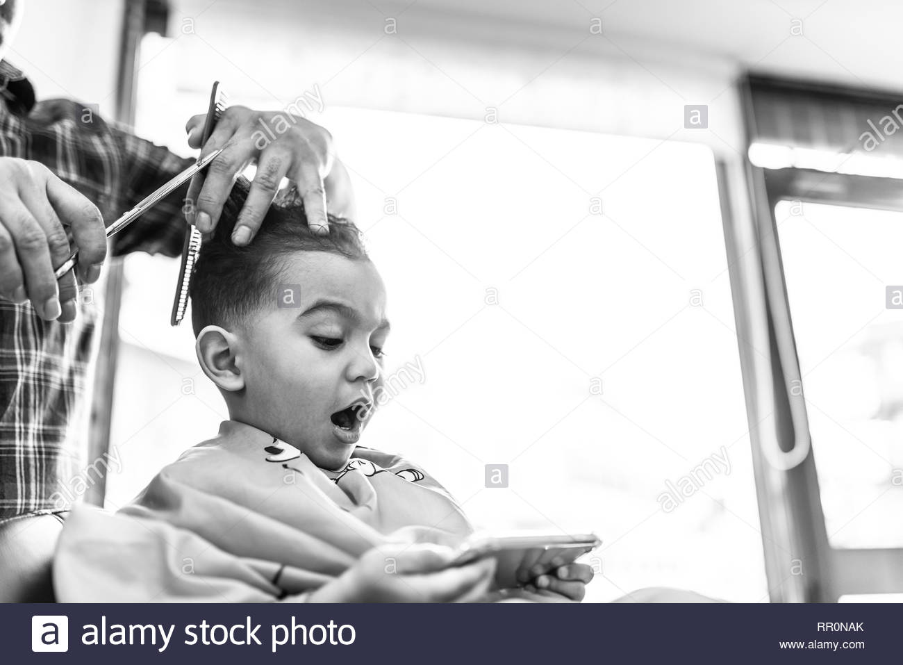 Cute Little Boy Getting a Hair Cut in a Barber Shop or Salon. Beauty Concept. - Stock Image