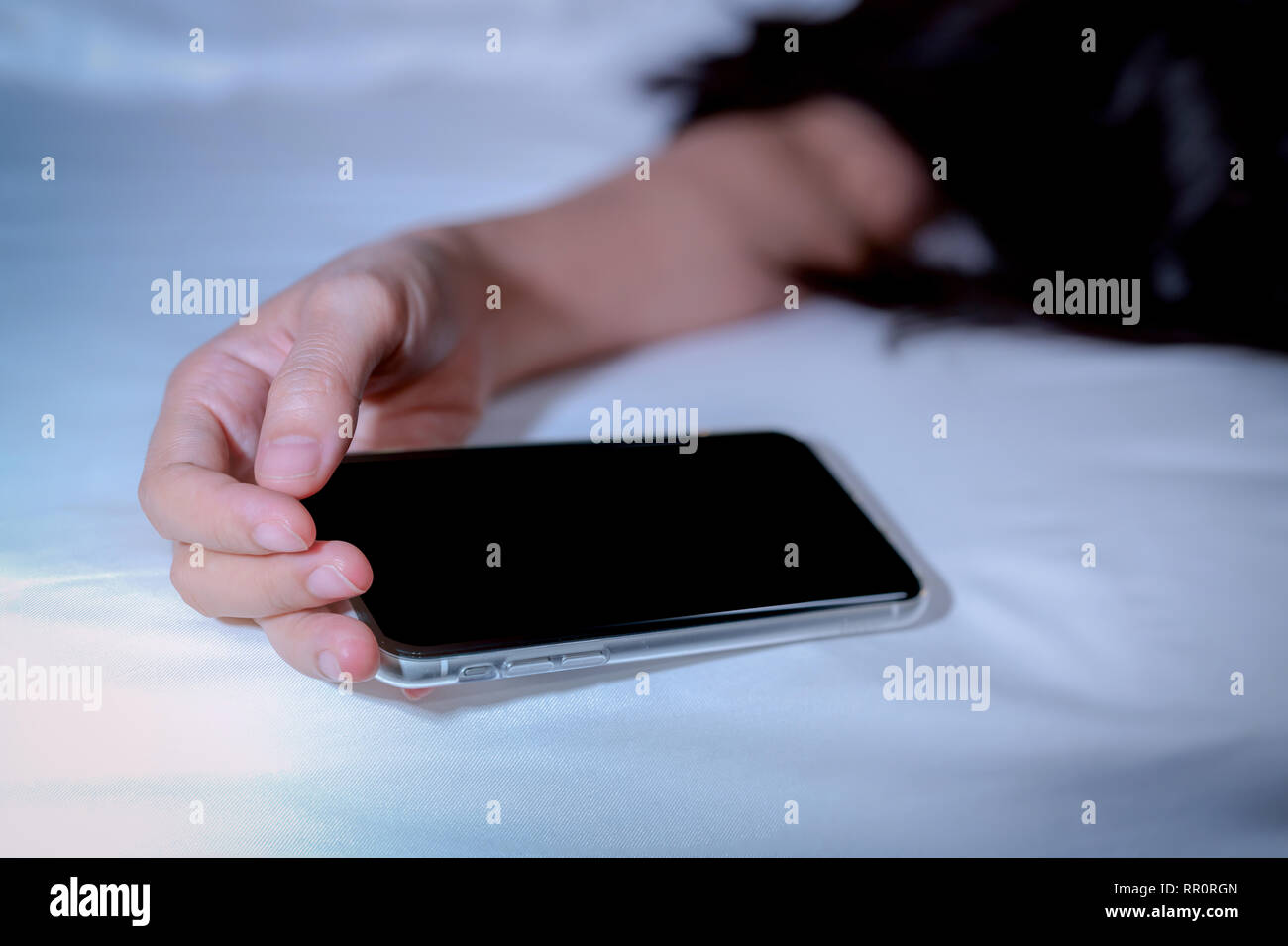 Asian woman sleeping in bed at home and hand holding mobile phone. Woman using smartphone in bedroom. Young woman addicted using smartphone. Texting o - Stock Image