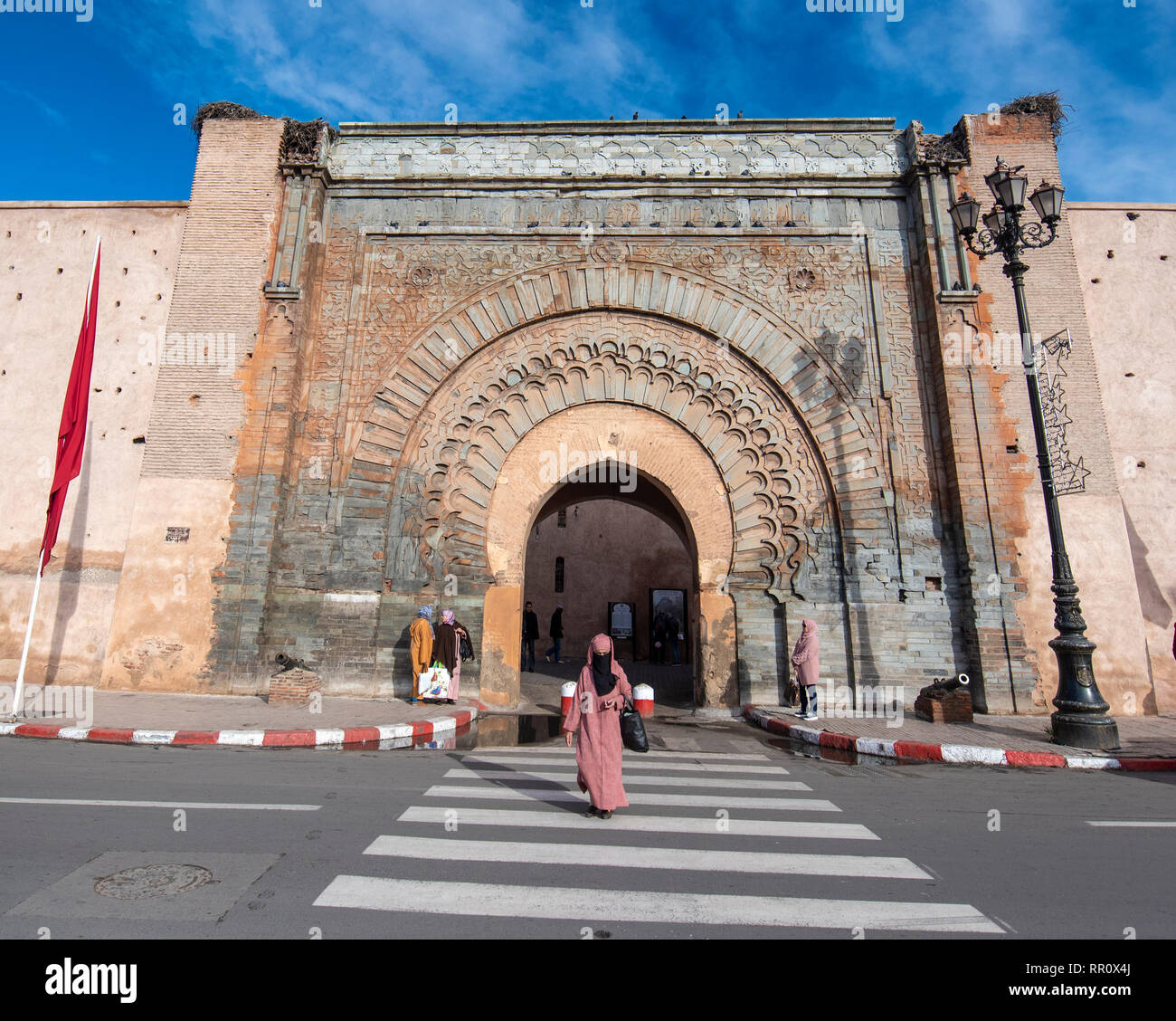 Arab woman crossing a pedestrian path in front of City gate Bab Agnaou . Entrance to the old city - the medina of Marrakech, Morocco Stock Photo