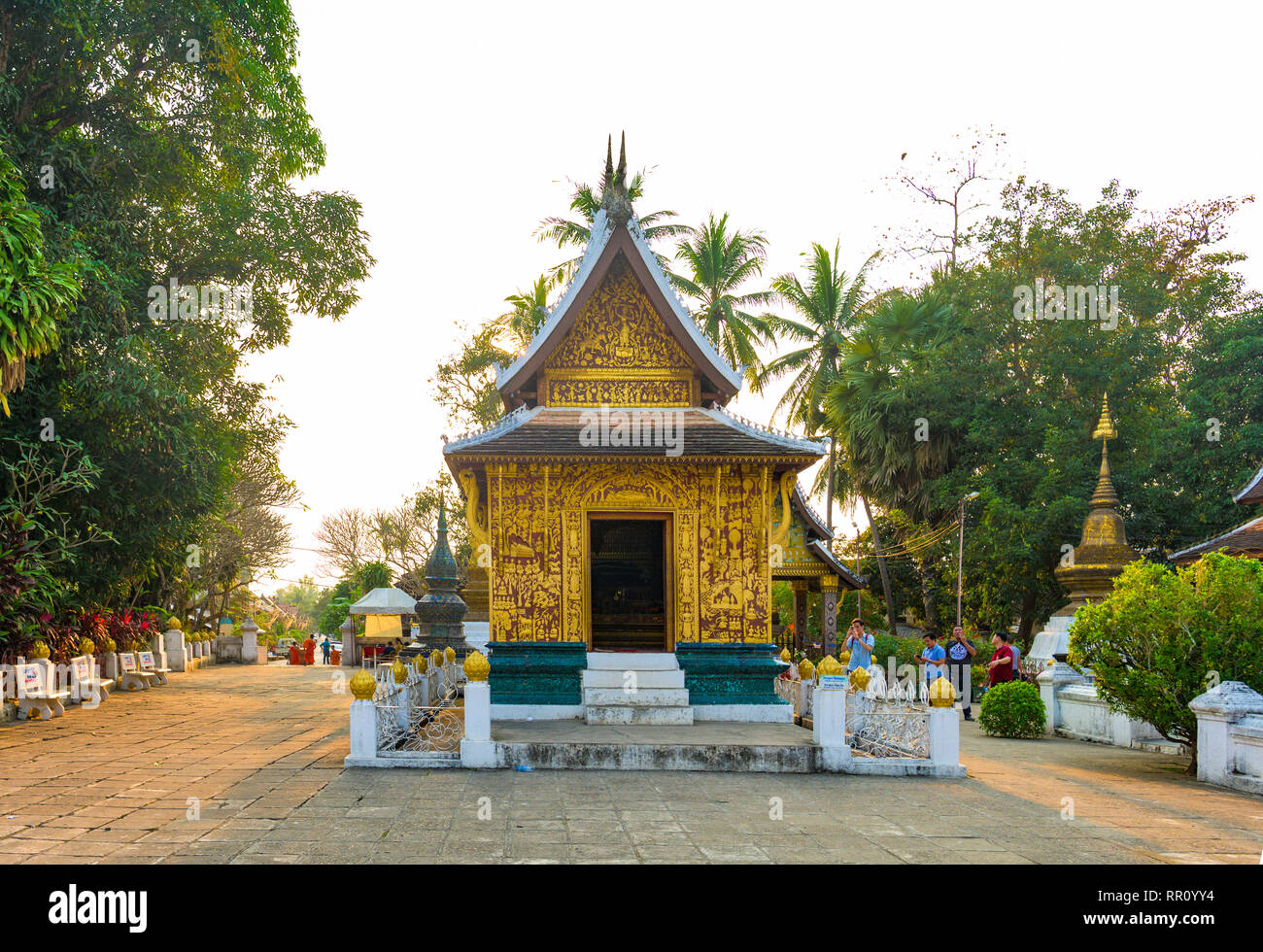 LUANG PRABANG - LAOS - 11 FEBRUARY 2019 Some tourists are walking and taking photos at the beautiful Wat Xieng Thong (Golden City Temple) at sunset in Stock Photo