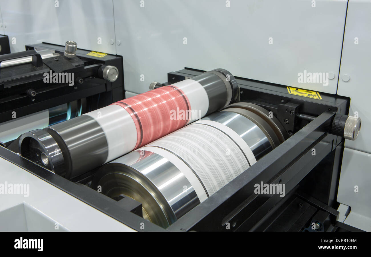Flexography printing process on in-line press machine. Photopolymer plate stuck on printing cylinder, substrate is sandwiched between the plate and th Stock Photo