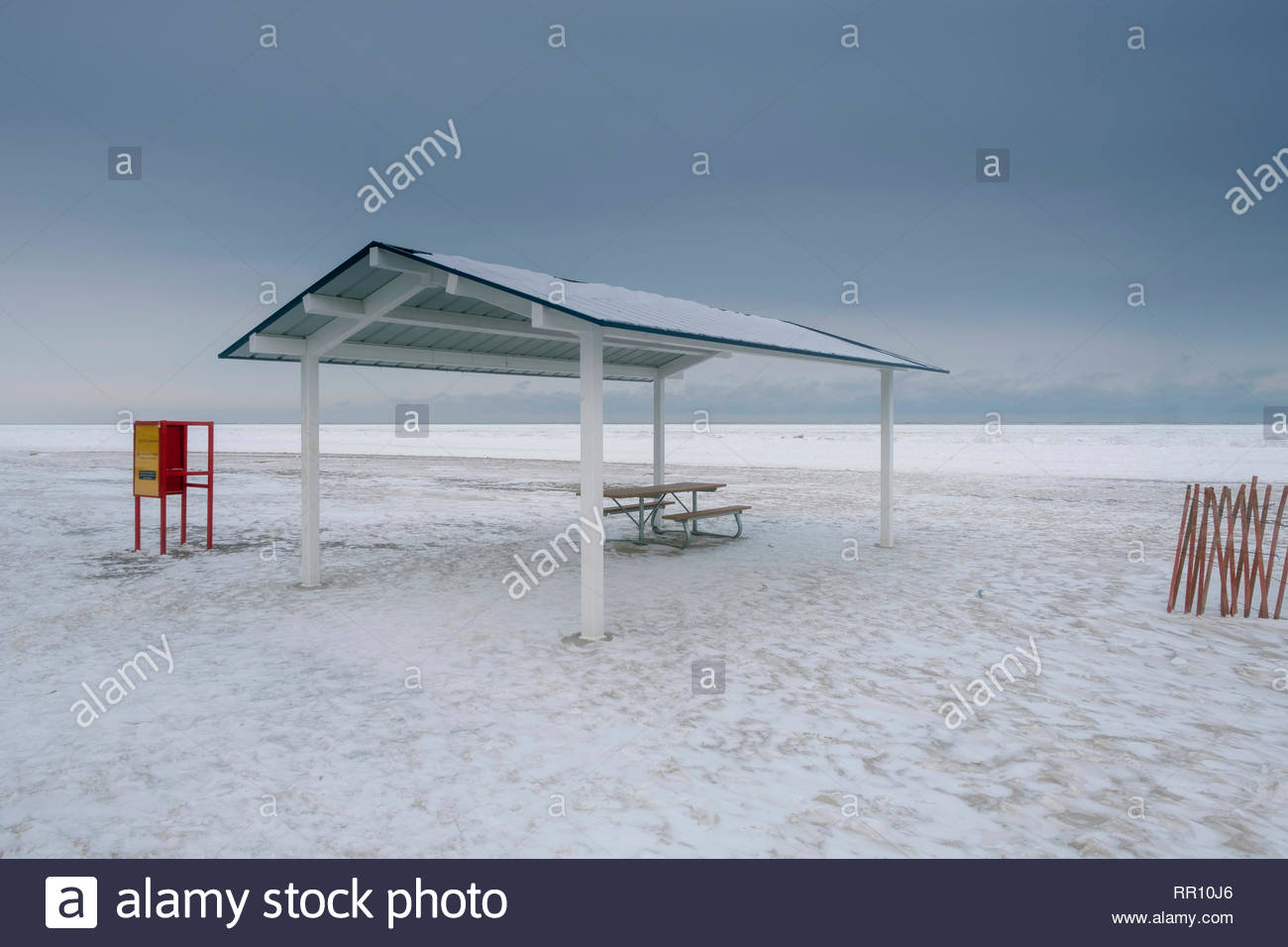 White and blue painted wood beach shelter on frozen beach, red metal signage, red fencing, frozen lake, soft blue sky, Port Dalhousie, Canada - Stock Image