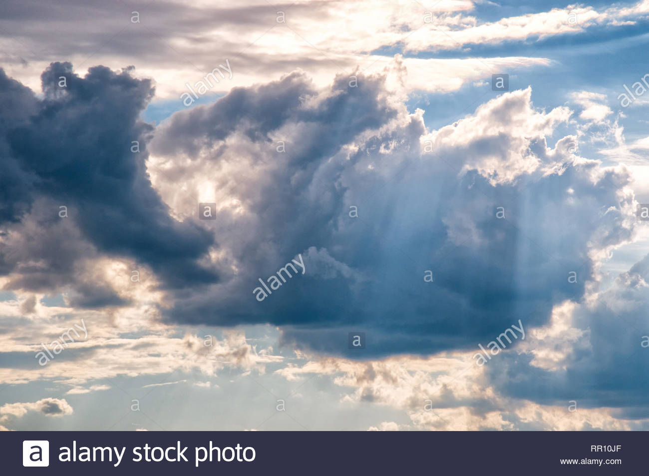 Moody grey blue clouds in sky with sun rays - Stock Image