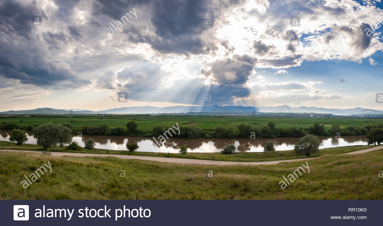 Romania nature landscape scene with reflection of clouds in river and sun rays in wispy grey clouds - Stock Image
