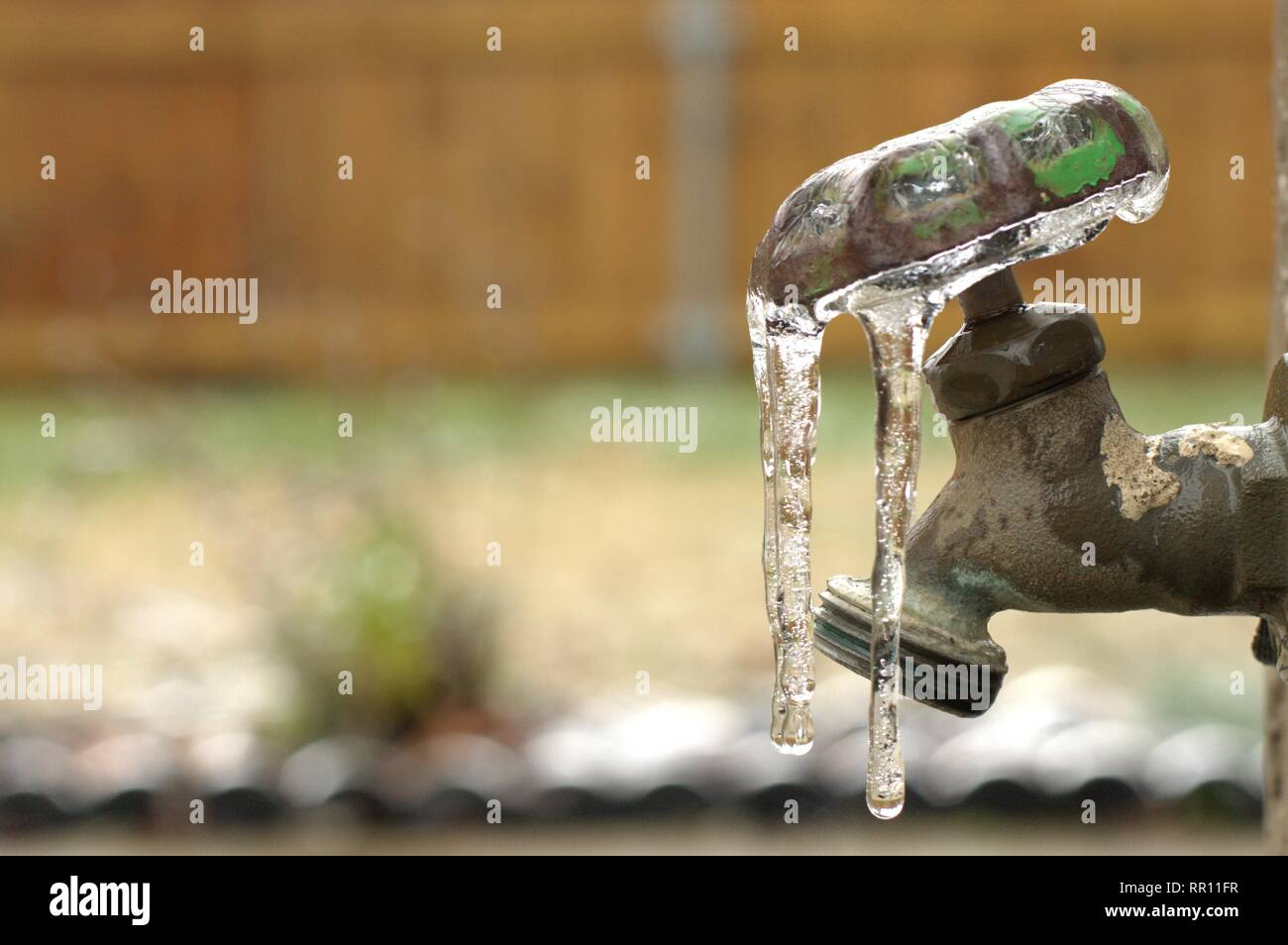 A frozen water spigot covered in ice. - Stock Image