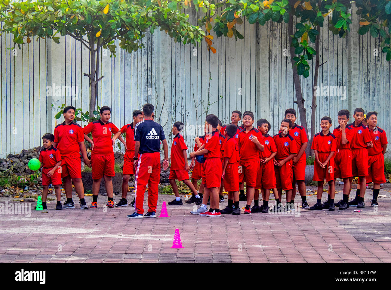 Schoolchildren in red sports uniform  their teacher playing a ball game in Jimbaran Bay Bali Indonesia. - Stock Image