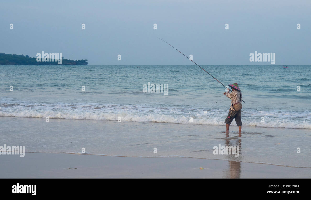 Lone fisherman wearing a conical hat fishing with a rod off the beach at Jimbaran Bay Bali Indonesia. Stock Photo