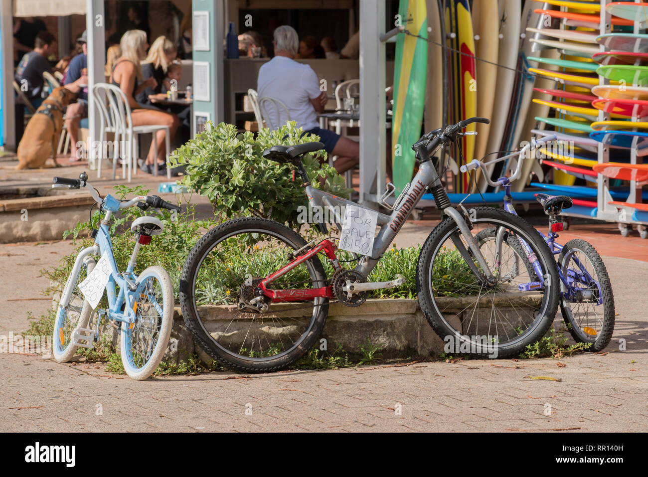Children's used or second hand bicycles for sale outside a surf shop