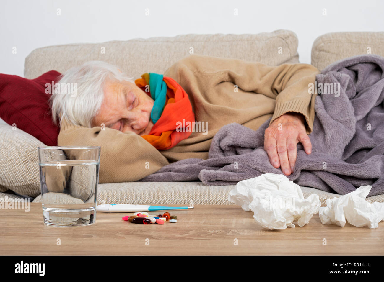 Senior woman feeling sick is lying on the couch wrapped in a blanket - Influenza, sore throat, headache - Medication, tissues and water in front of he - Stock Image