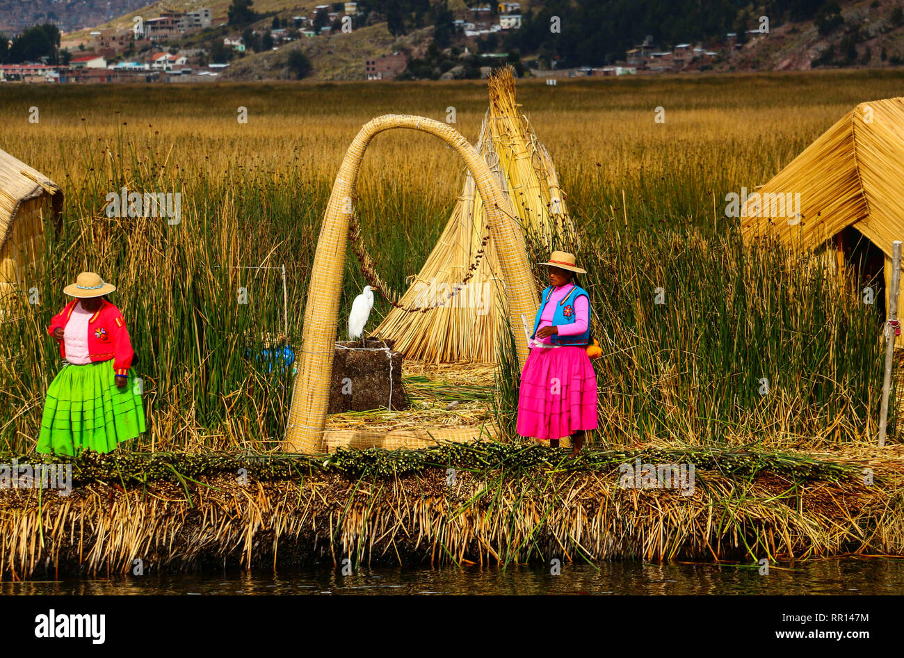 PUNO, PERU - NOVEMBER 11, 2015: Women in traditional attires on Uros Islands, lake Titicaca, Peru - Stock Image