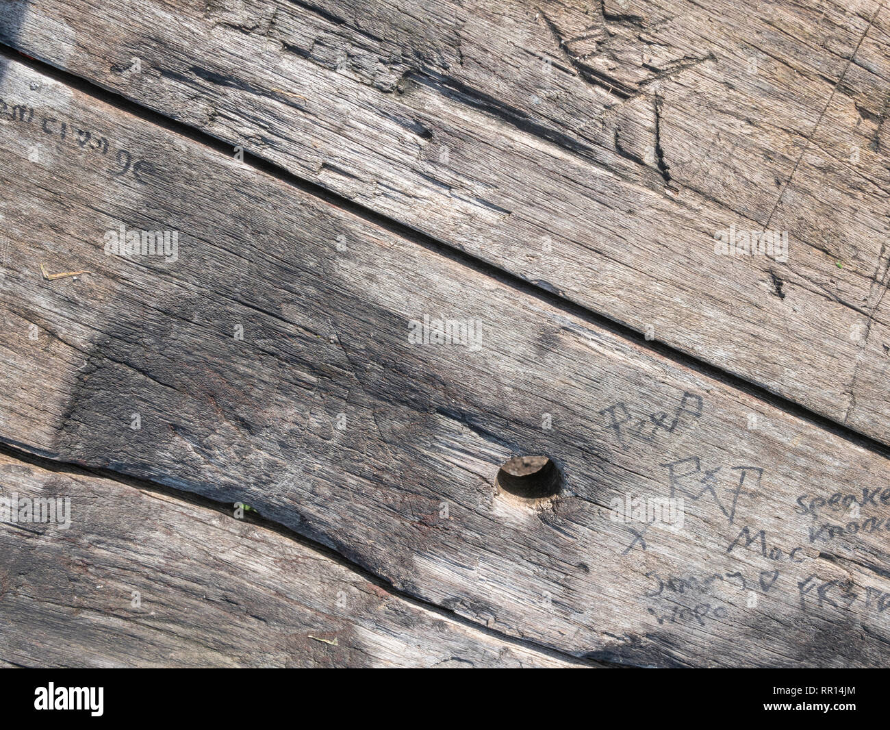 Weathered and gnarled wooden outdoor table top texture in sunshine. - Stock Image