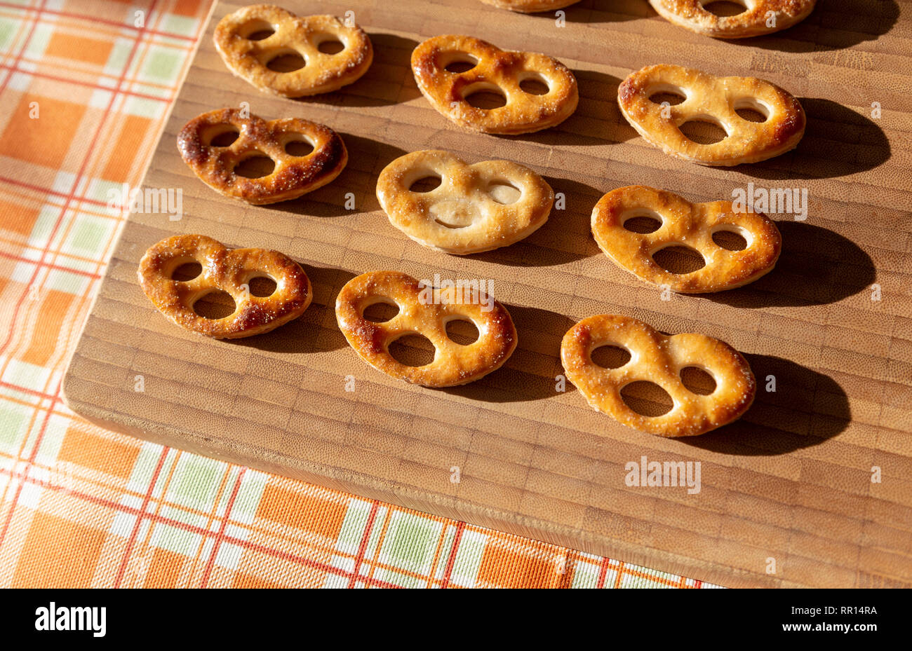 Several biscuits on cutting board with one different from others - Stock Image