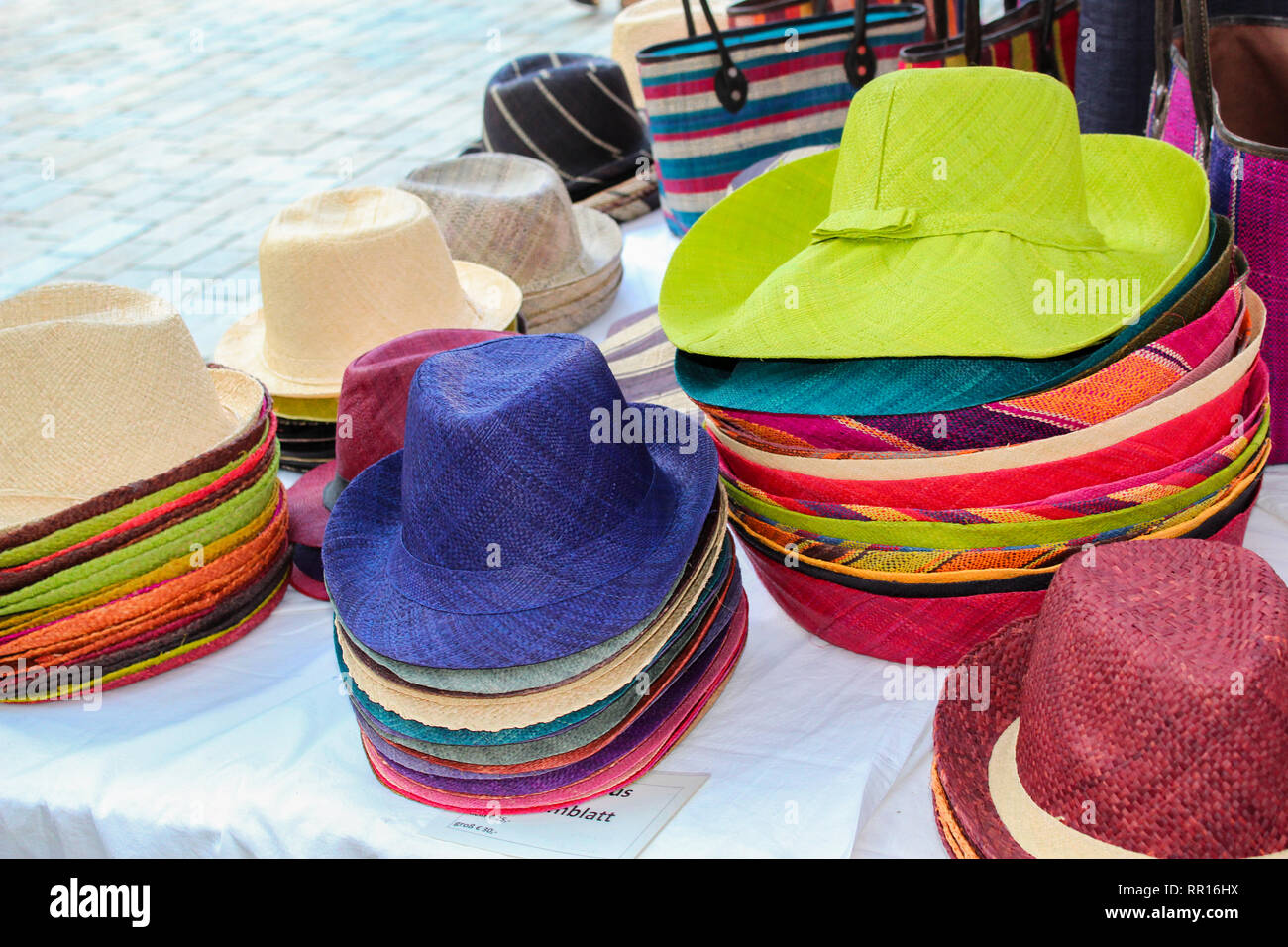 4c5437a13ba Colorful straw hats and bags at a Market for sale - Stock Image
