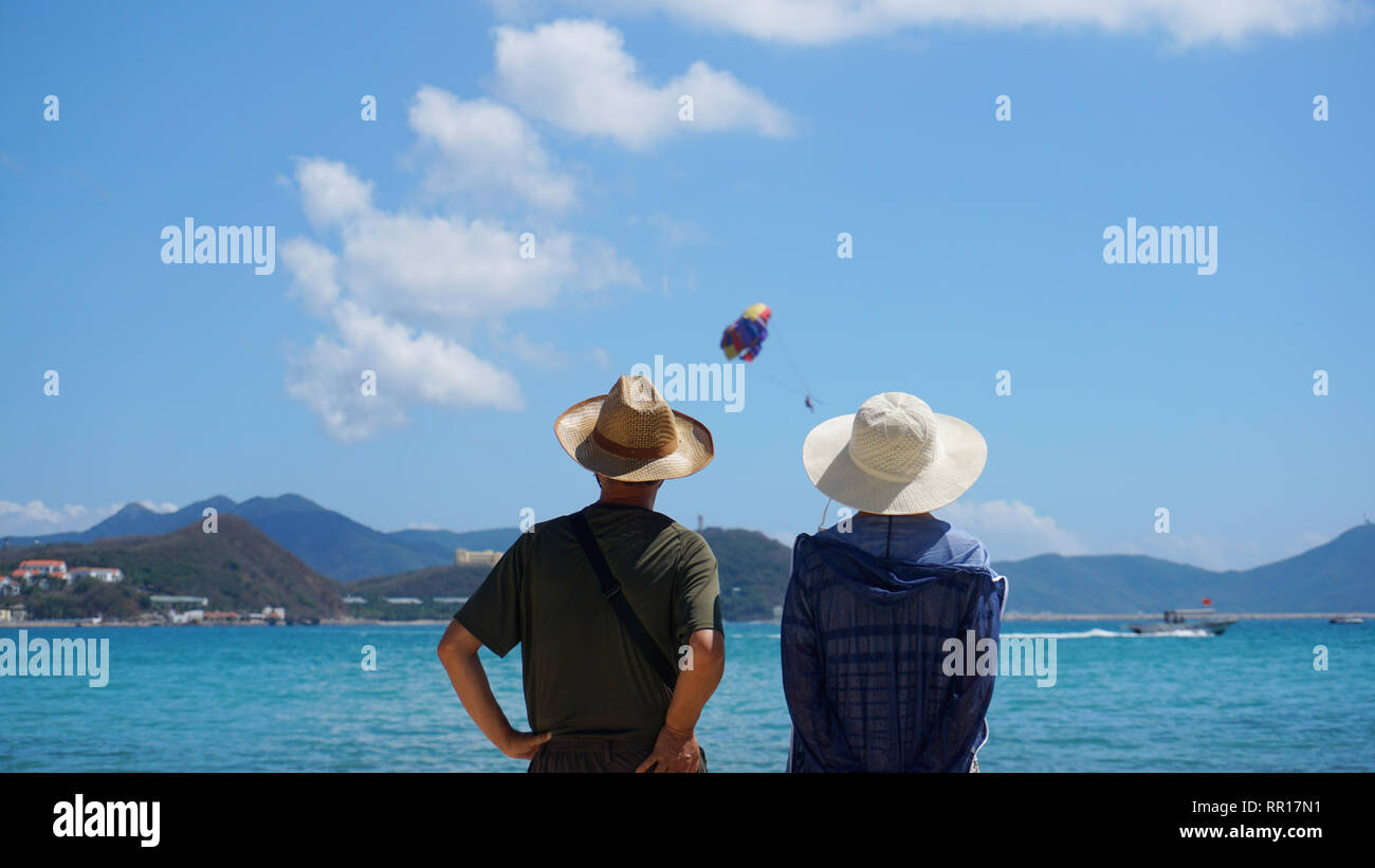 Asian Couple Man and Woman in hats staying on Beach seaside and look at the hot balloon in the sky - Stock Image