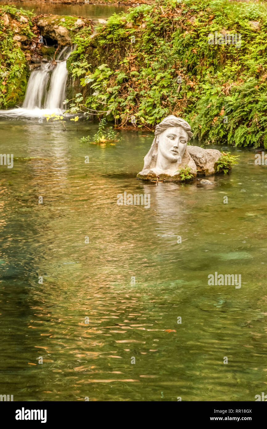 River Erkyna, the one of two rivers of feminine name in Greece, in the city of Livadeia, Central Greece. The bust personifies goddess Erkyna. - Stock Image
