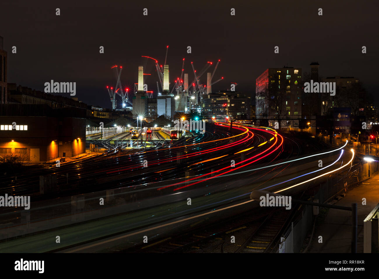Lights trails from Southern & Southeastern trains approaching & departing from London Victoria in the evening rush hour with Battersea power station - Stock Image