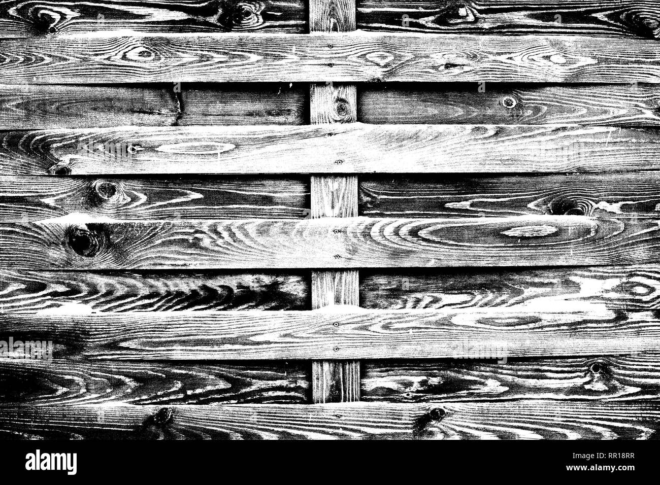 Old wooden fence of unplanned planks, black and white high contrast texture - Stock Image