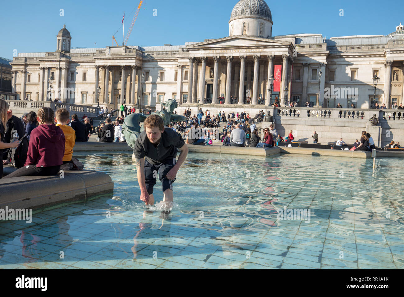 Homeless man looking for coins in water of the fountain in Trafalgar Square. Tourists and visitors enjoying the warm spring like weather in February - Stock Image