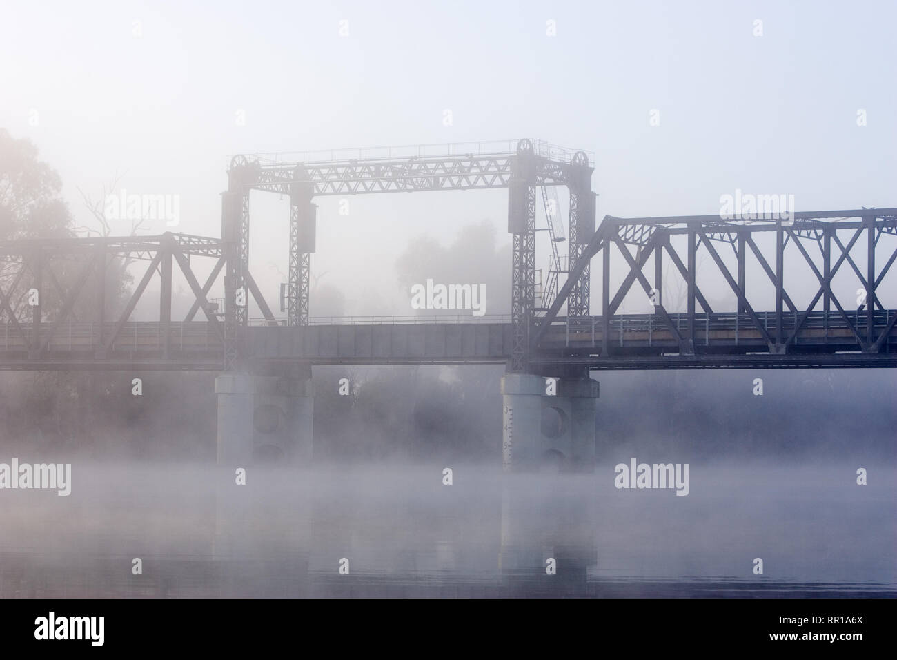 Old lift-span bridge over the Murray River, down stream from Mildura, photographed on a foggy winters morning, built in 1928. Stock Photo