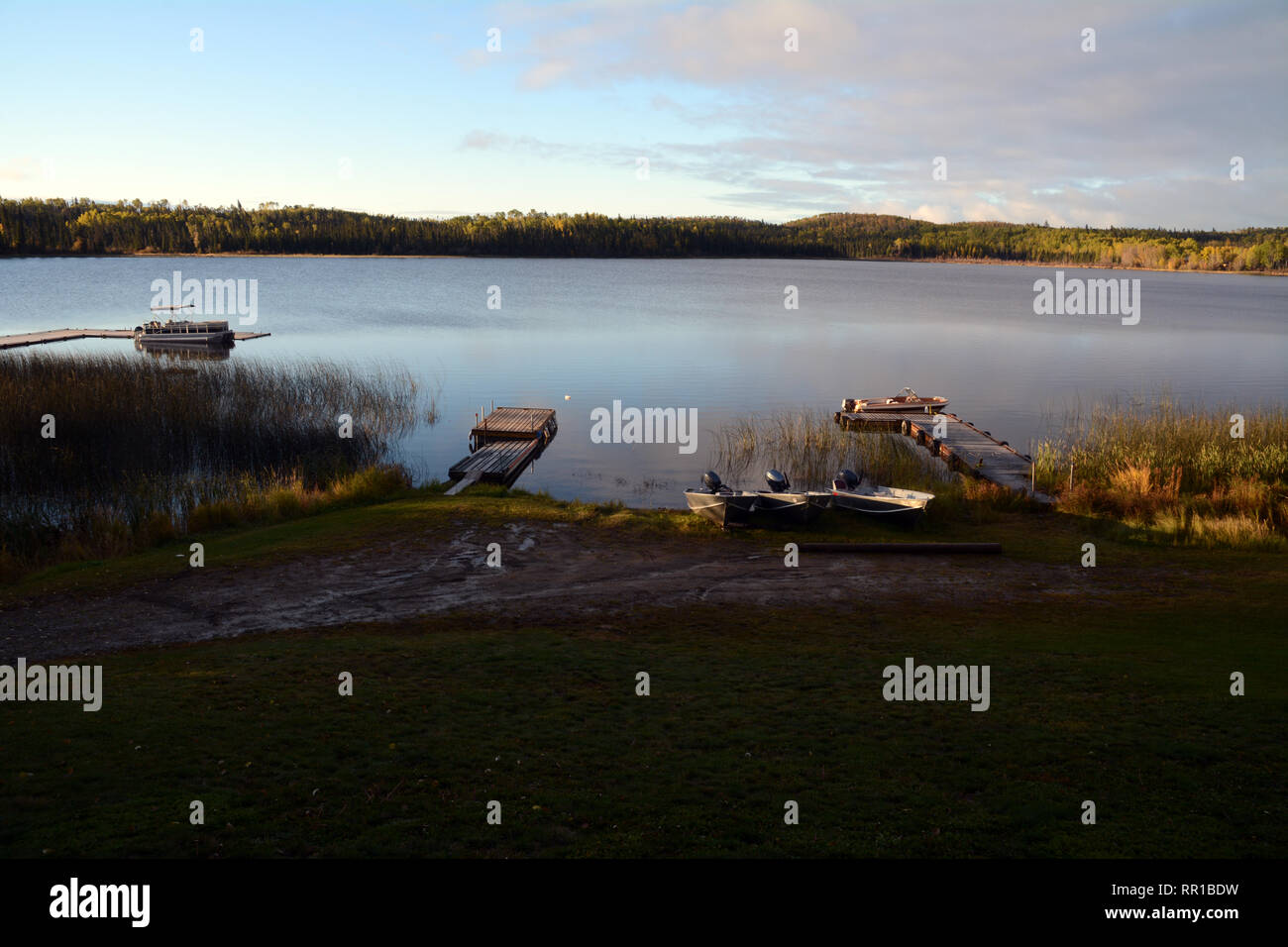 Docks and boats on the shores of Otter Lake at dawn, in the boreal forest community of Missinipe, Saskatchewan, Canada. Stock Photo
