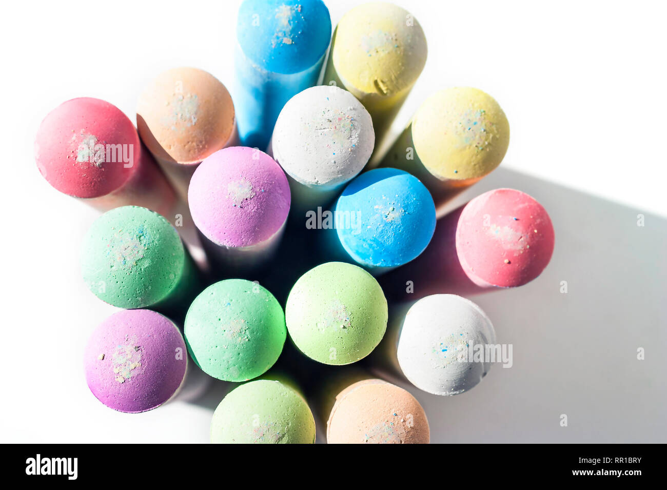 Pack of Jumbo Sidewalk Chalk, Assorted Colors, Bold Tips Casting Shadow on White Background. Top View. - Stock Image