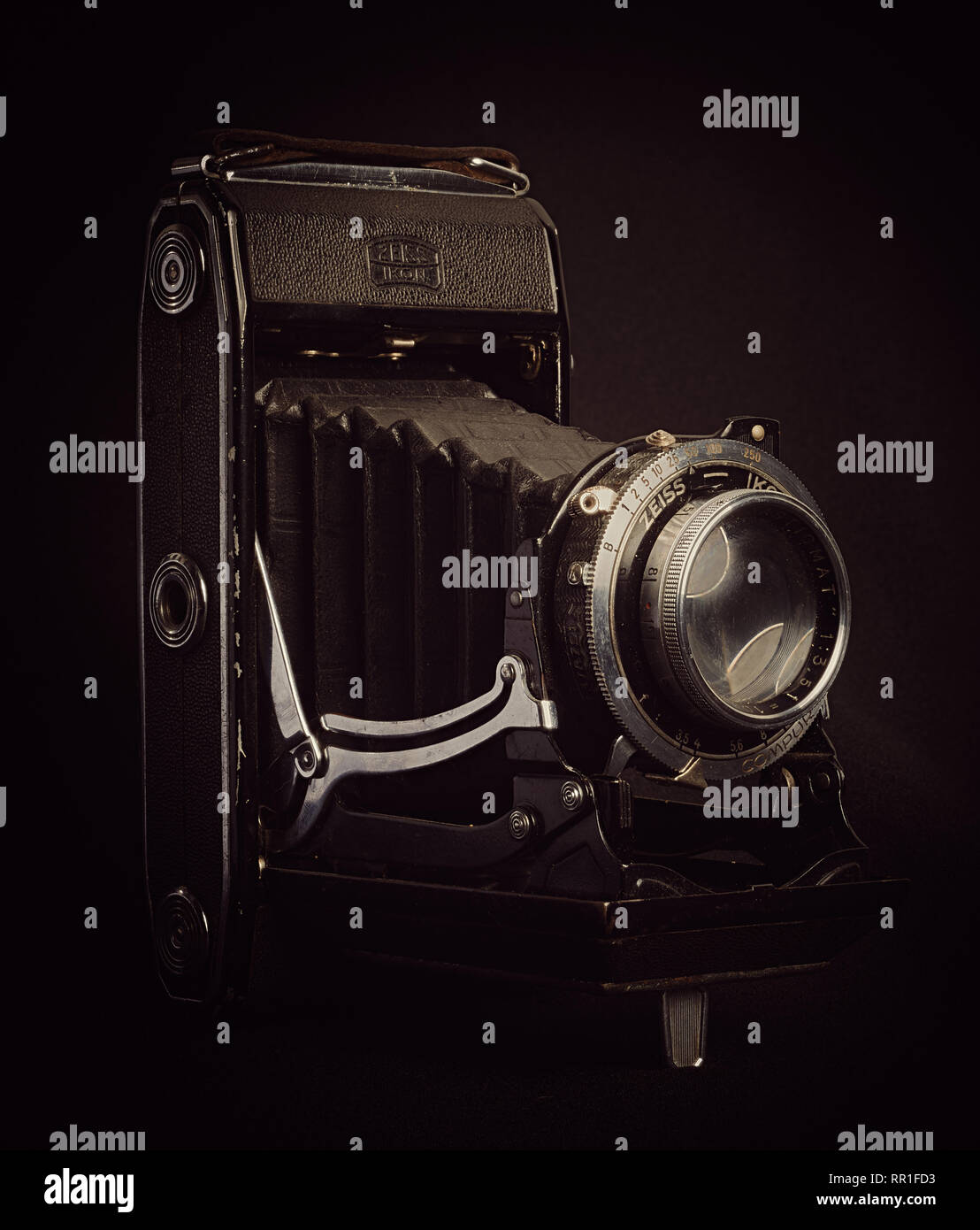 Vertical aspect right side view of a vintage bellows film camera against a black background. - Stock Image