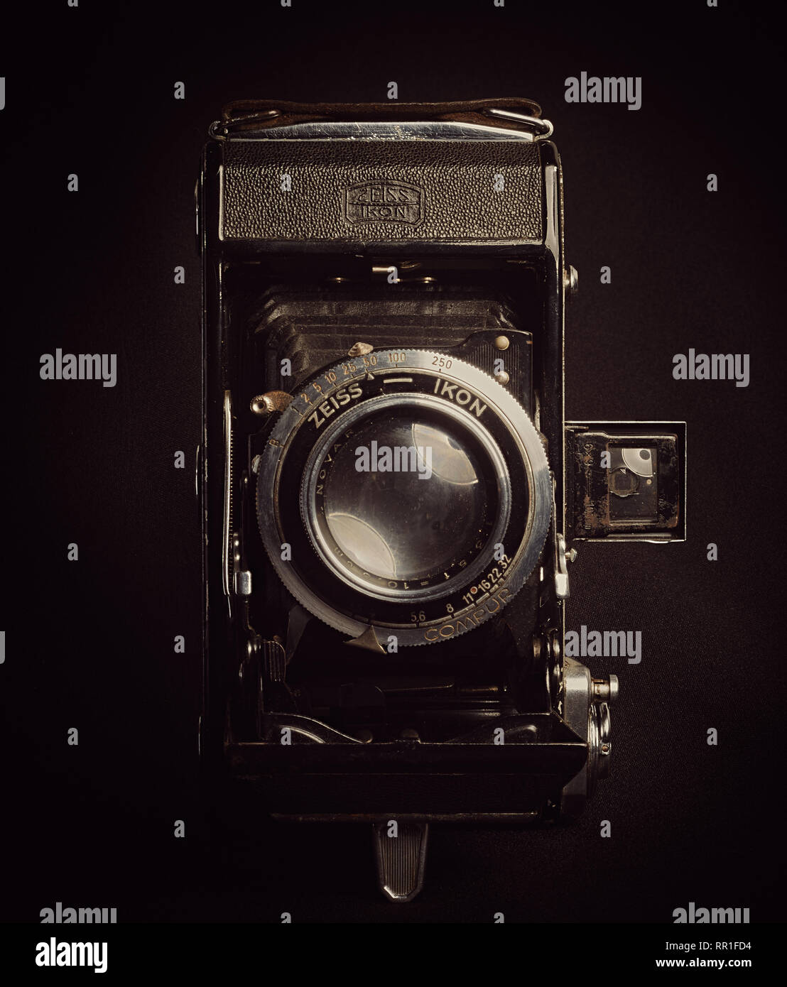 Vertical aspect front view of a vintage bellows film camera against a black background. - Stock Image