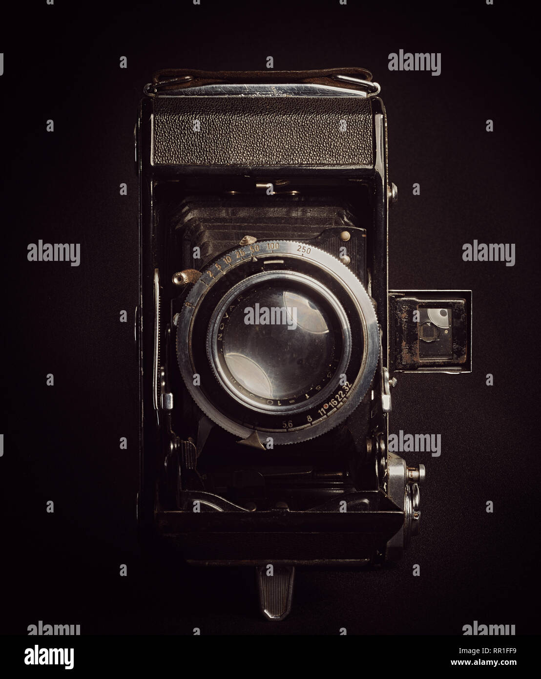 Vertical aspect front view of an unbranded vintage bellows film camera against a black background. - Stock Image