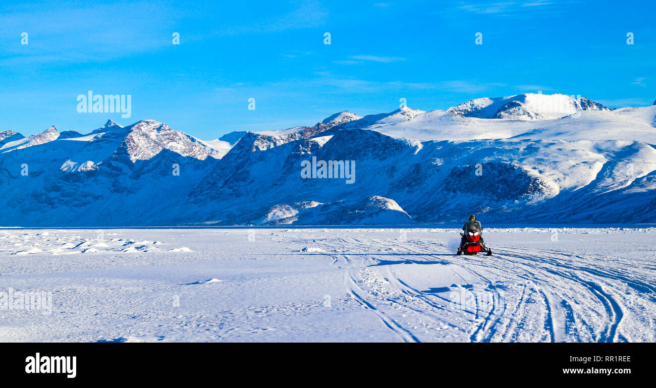 Snowmobiler driving over the Cumberland Sound to get to their fishing shack in search of turbot. - Stock Image