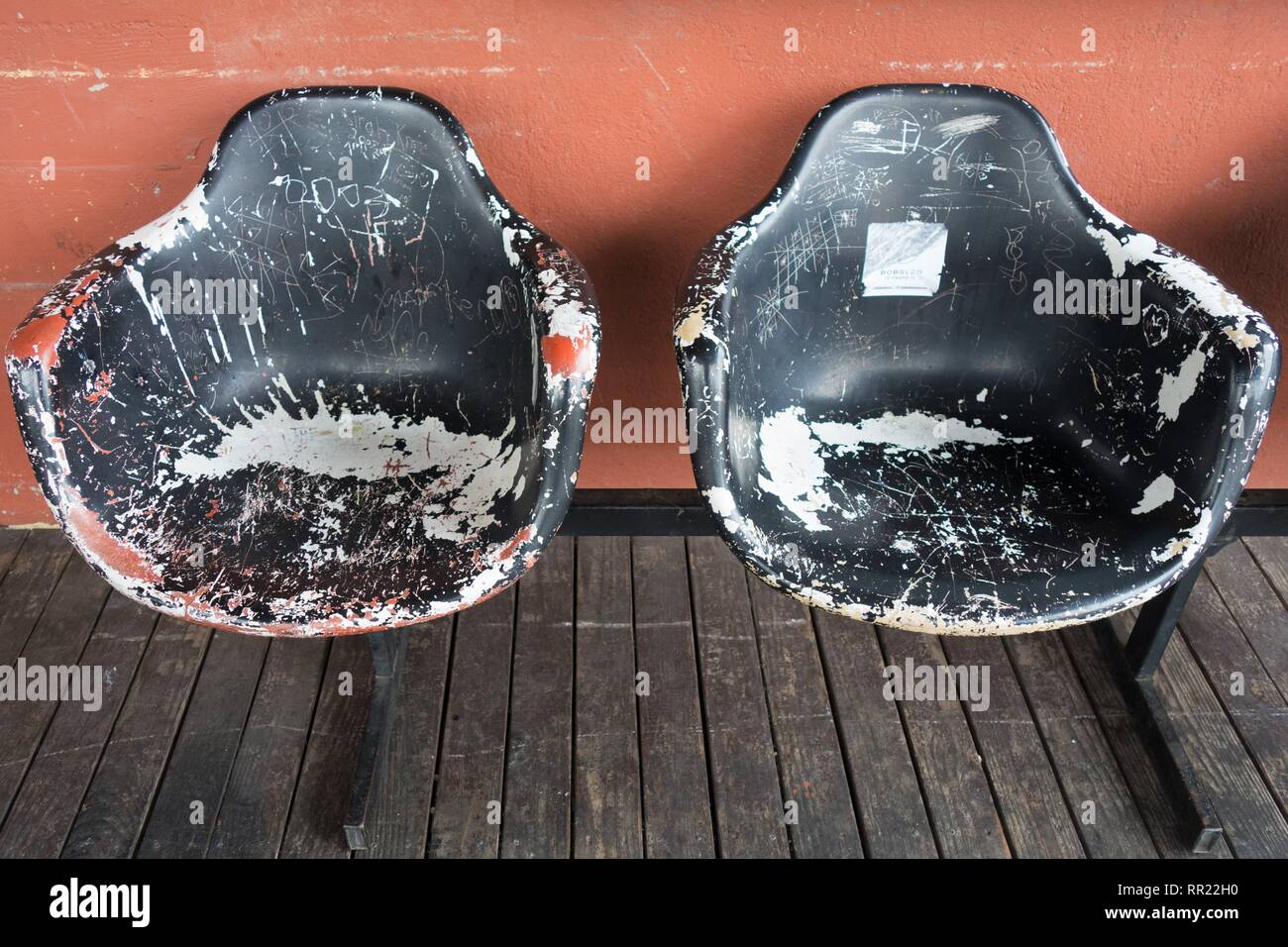 Scuffed up and scratched fiberglass chairs. - Stock Image