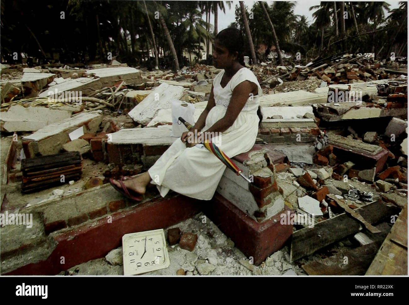. After the Tsunami: Rapid Environmental Assessment. . Seenigama, Sri Lanka (26 January 2005). A Sri Lankan woman sits among the rubble of her house destroyed by the tsunami as aid workers heip clear debris at Seenigama Village, some 90 kilometres south of the Sri Lankan capital Colombo. © Prakash Singh/AFP/Getty Images to measures to relieve hardship such as confirmation that the salaries of civil servants killed in the disaster would continue to be paid to what would have been their retirement age and full pension rights guaranteed thereafter. The donor community and government reacted quick - Stock Image