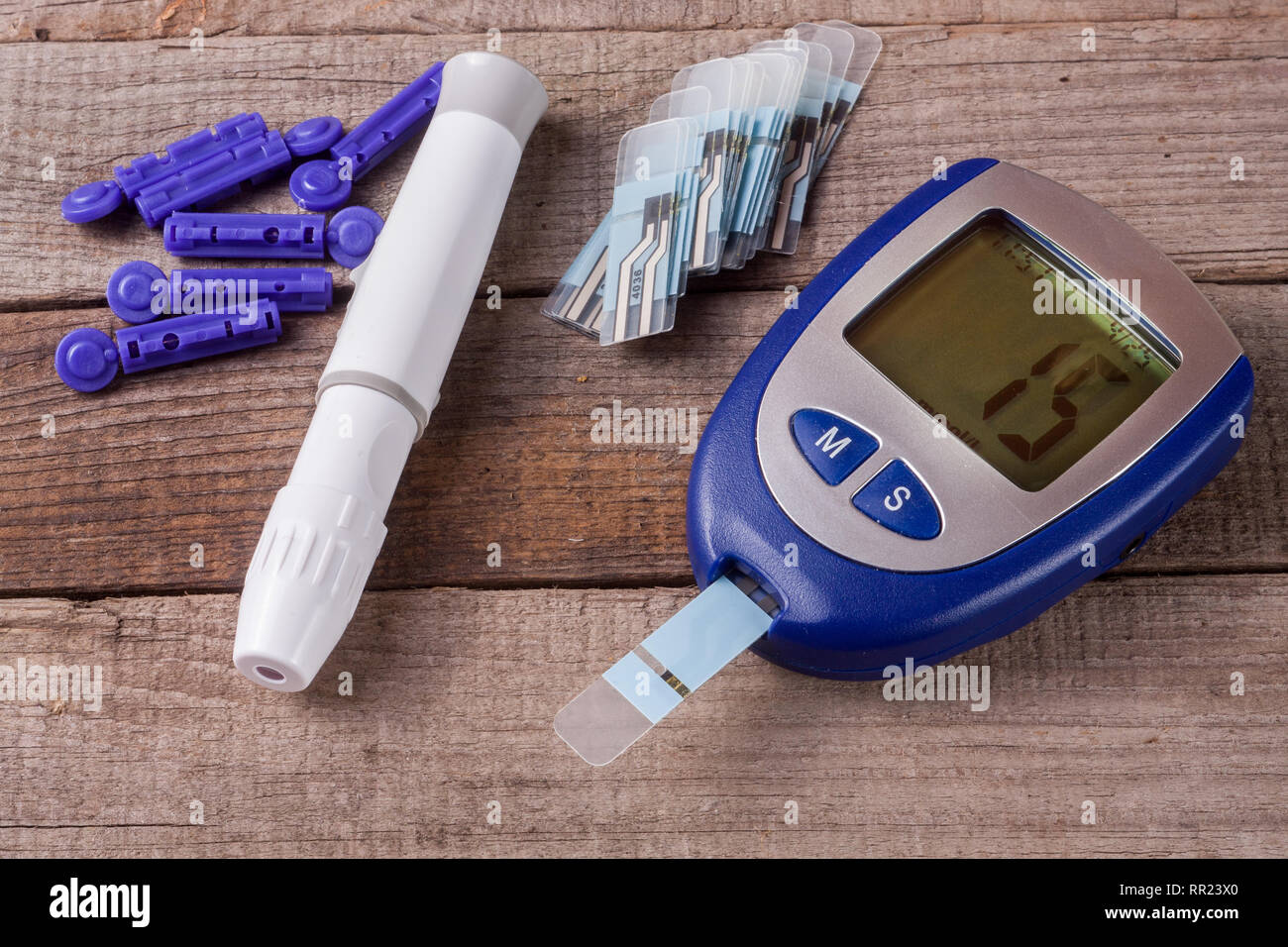 blood glucose meter on an old wooden background - Stock Image