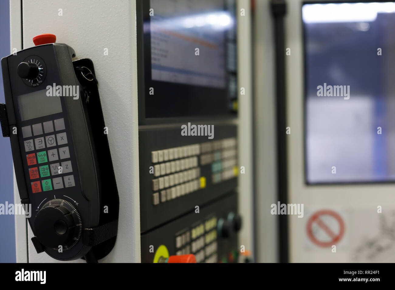 Pendant manual remote control of 4 axis CNC lathe with handwheel and LCD screen. Selective focus. - Stock Image